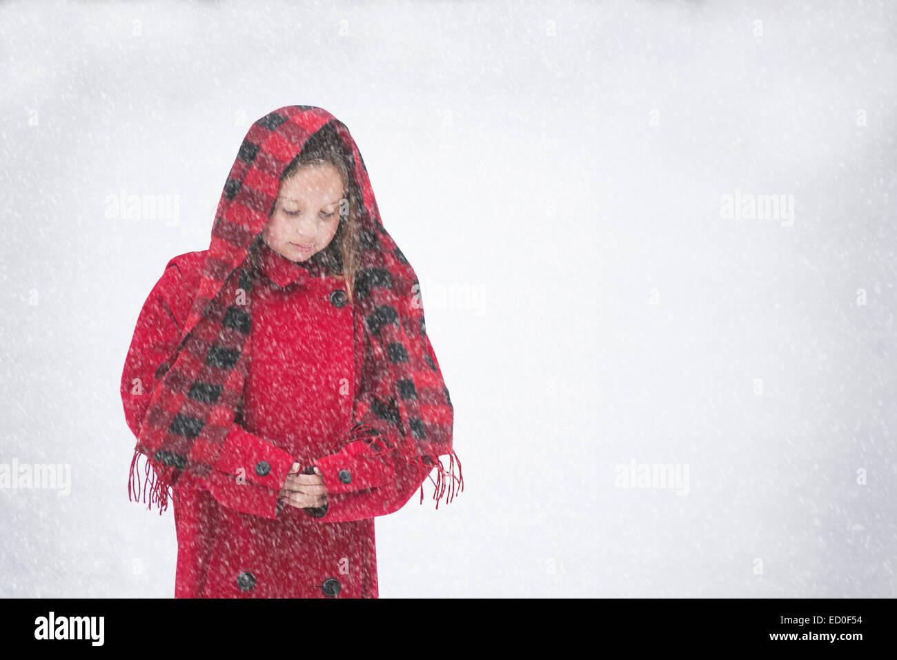 Chica (8-9) en la chaqueta roja en la nieve Imagen De Stock