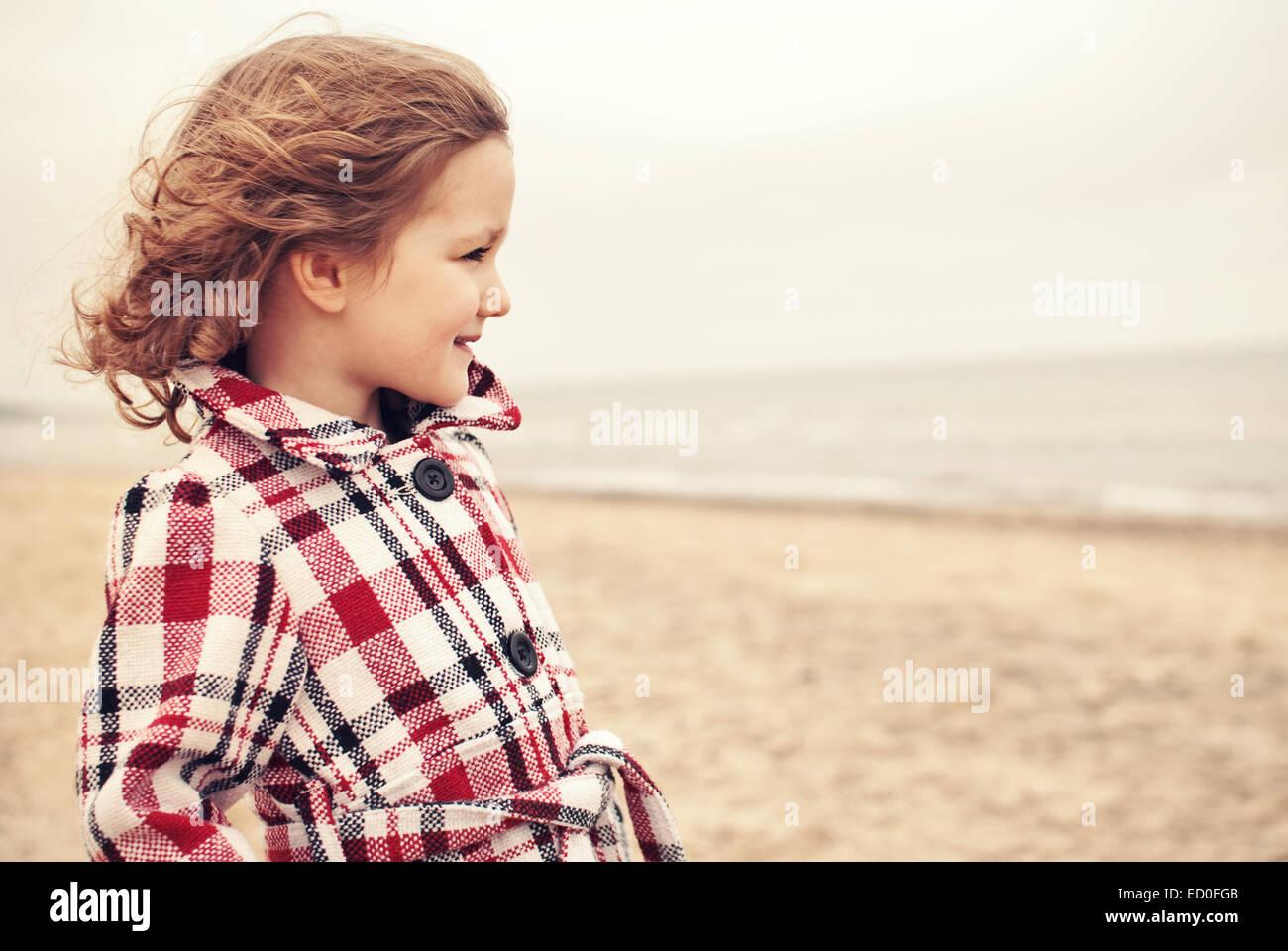 Niña pequeña (2-3) en escudo en la playa Imagen De Stock