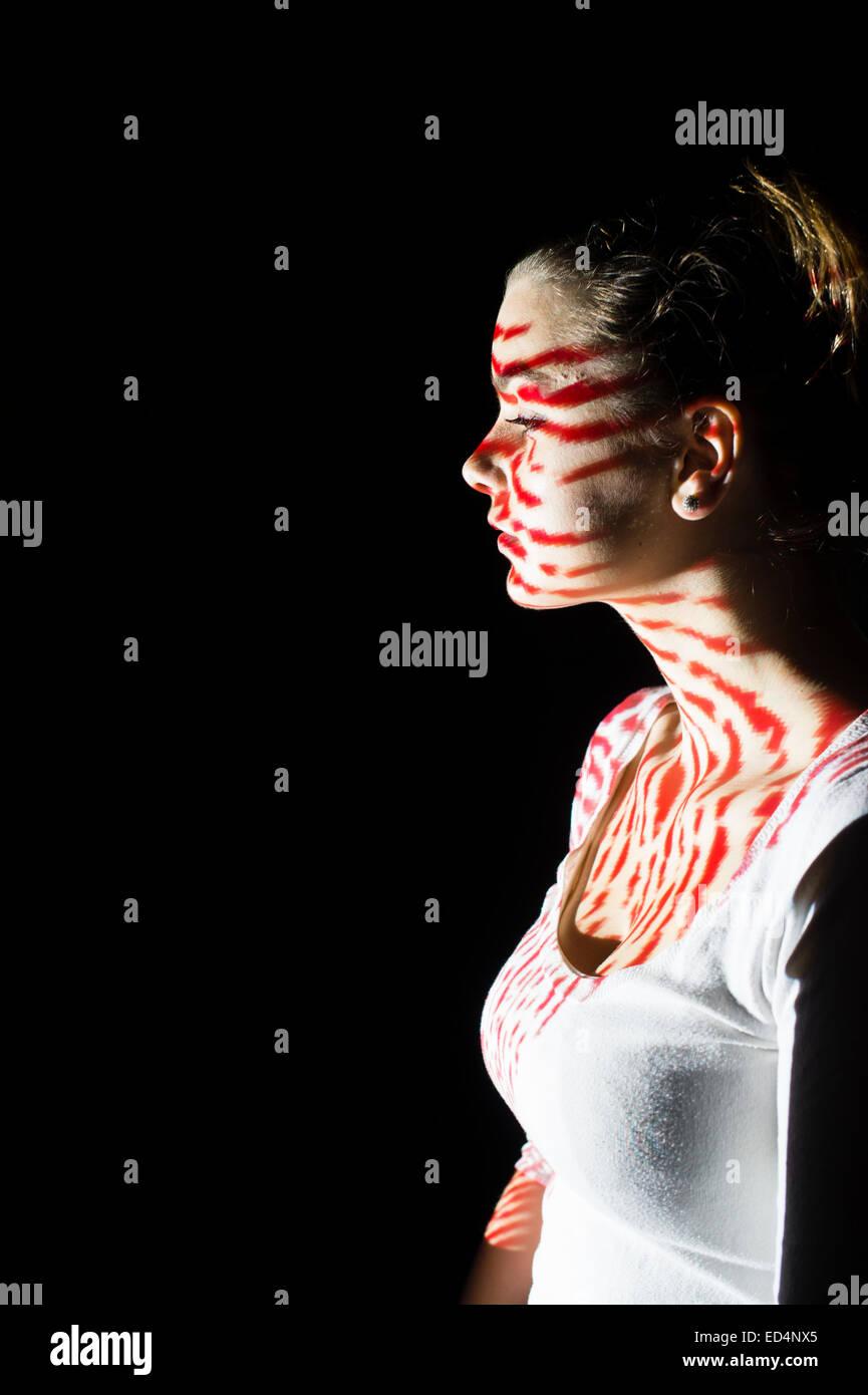 Arte Digital: una joven muchacha de perfil con la imagen de la huella digital modelo proyecta sobre su rostro. Imagen De Stock