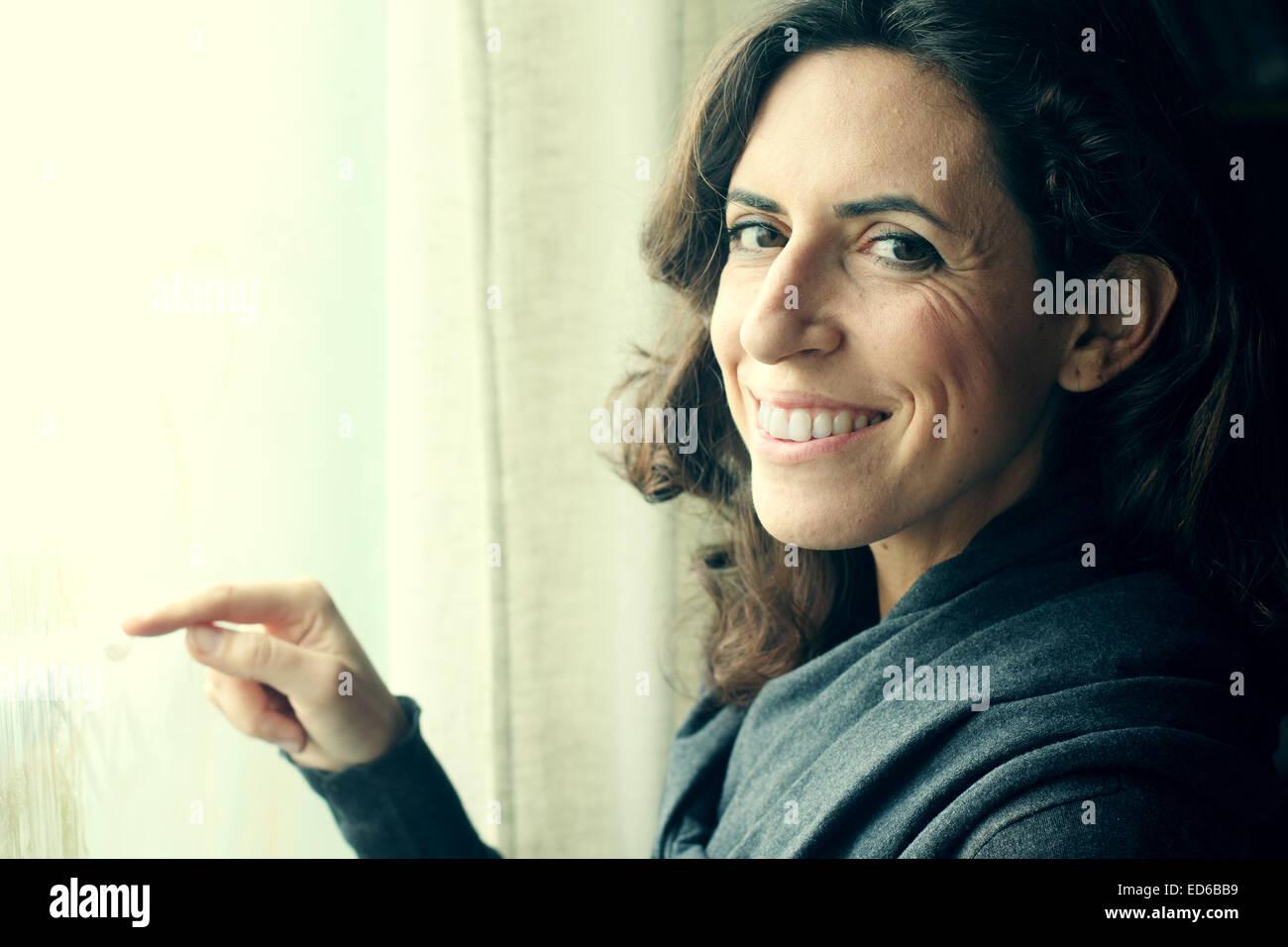 Retrato de hermosa mujer de 35 años de pie cerca de la ventana Imagen De Stock