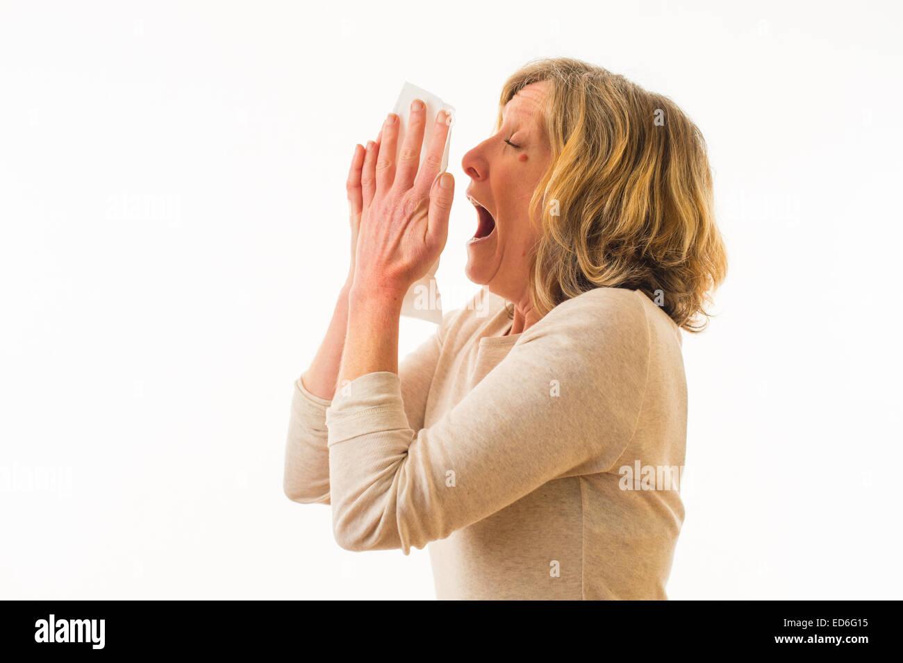 A cuarenta años de edad adulta caucásica sufriendo con un resfrío o gripe estornudos en un pañuelo Imagen De Stock