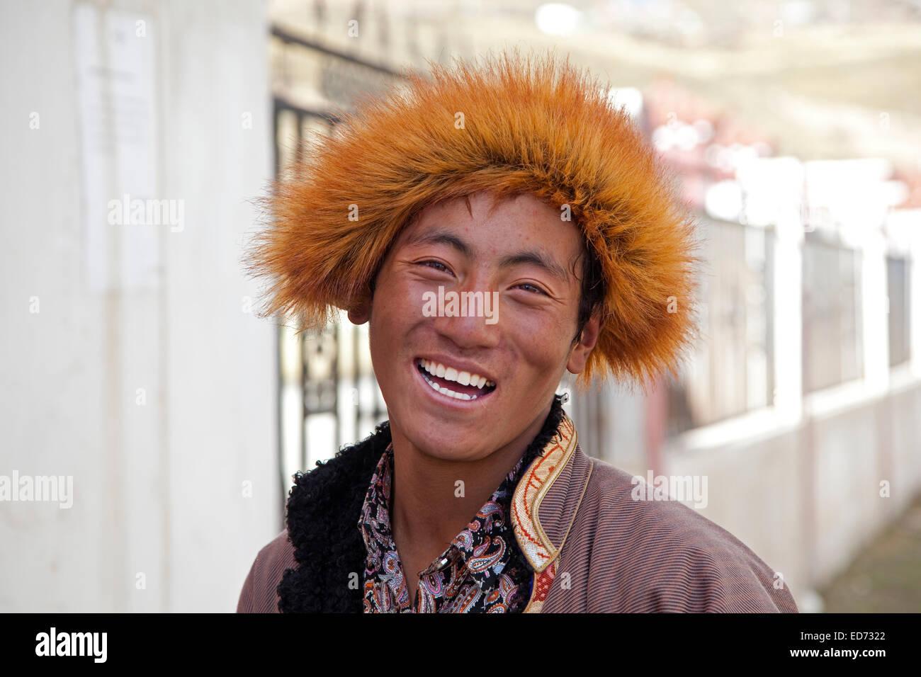Close Up retrato de sonriente hombre tibetano con sombrero de piel en la aldea Qagca / Cacagoin, provincia de Sichuan, Imagen De Stock
