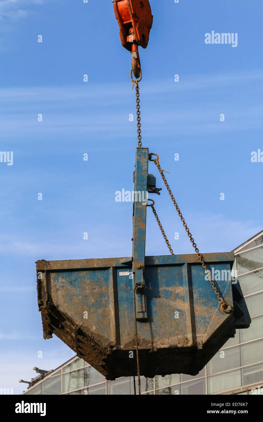 Grandes constructores skip levantada por una grúa durante trabajos de reurbanización en Londres Victoria Imagen De Stock