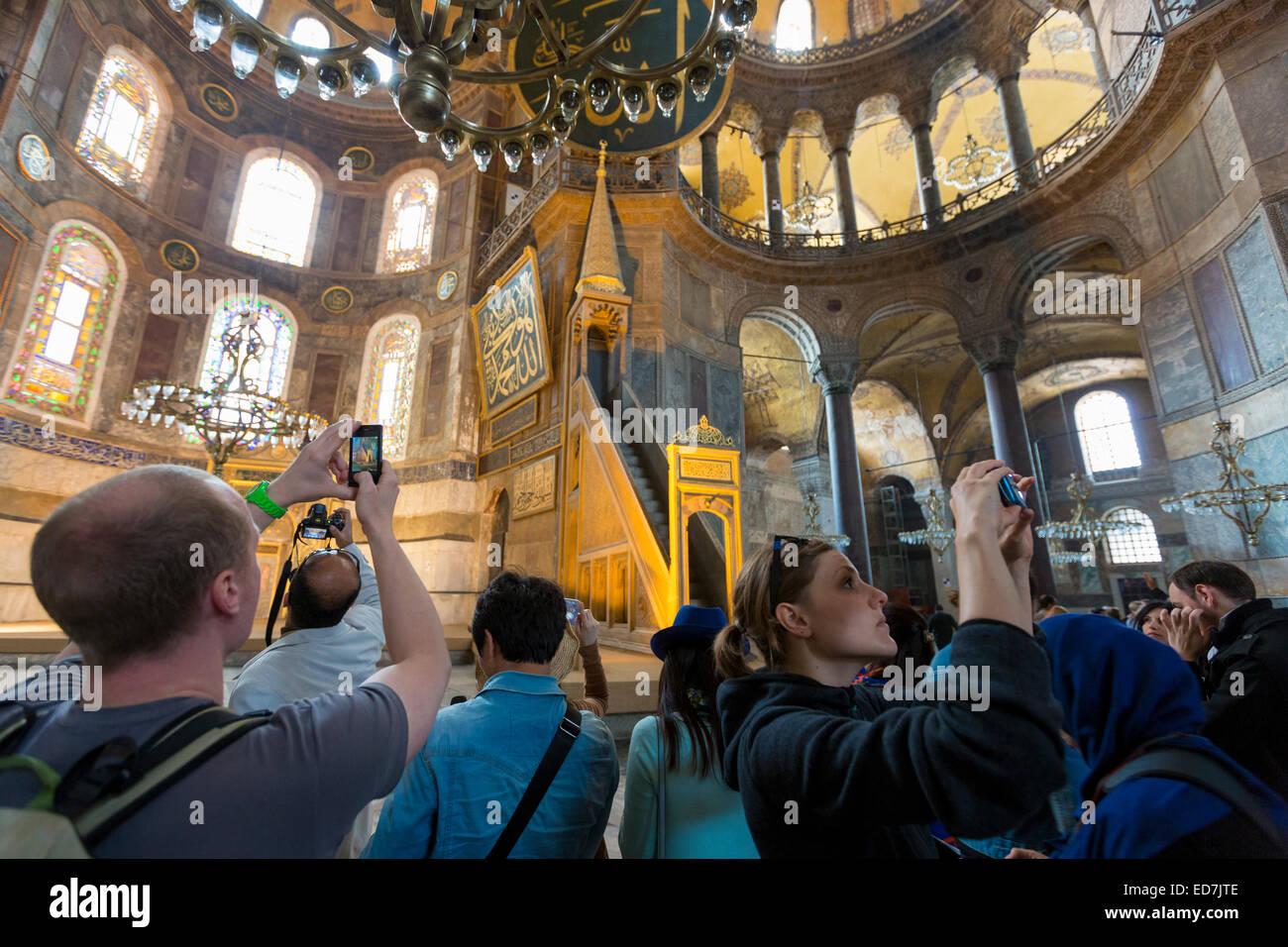 Los turistas en la Catedral de Santa Sofía Hagia Sophia, la mezquita de Ayasofya Muzesi, museo utilizando smartphones Imagen De Stock