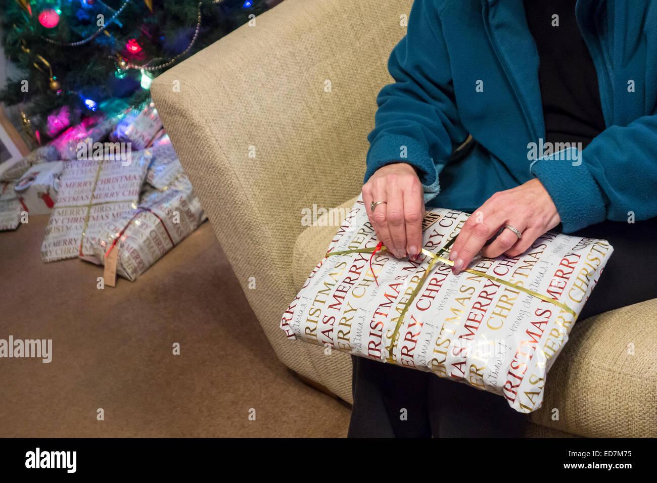 Una mujer mayor desenvolver un regalo de Navidad. Imagen De Stock