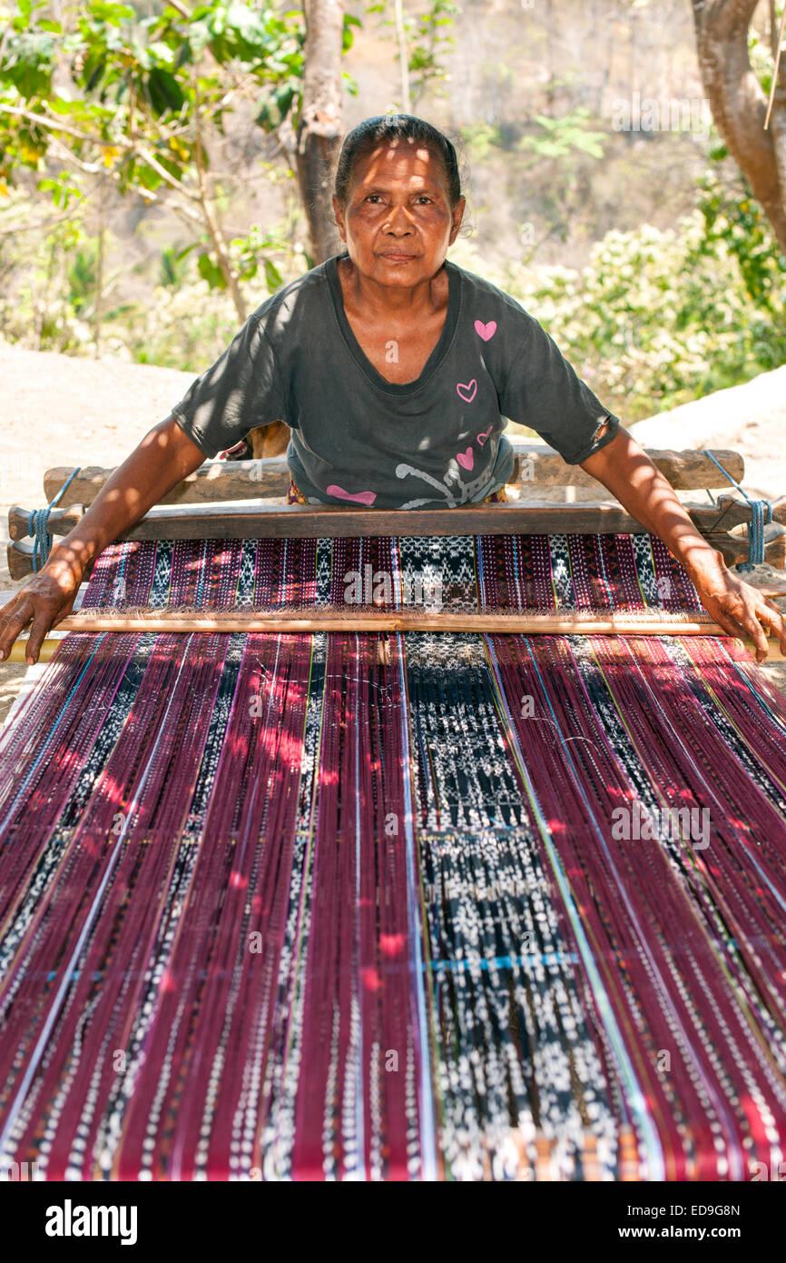 Mujer de Indonesia tejiendo sarongs tradicionales sobre el borde de la carretera en la isla de Flores en Indonesia. Imagen De Stock