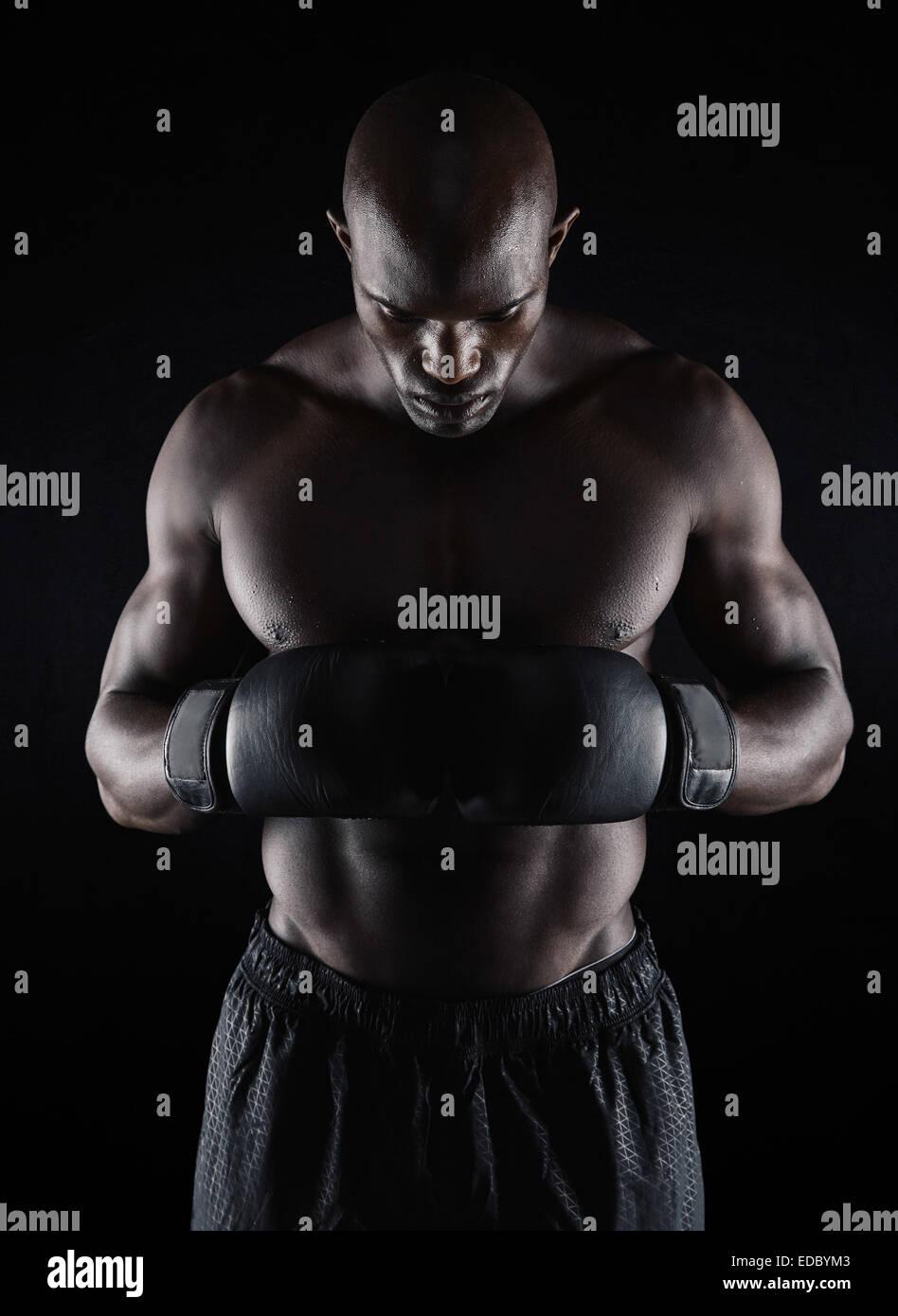Retrato de colocar joven llevando guantes boxeo mirando hacia abajo sobre fondo negro. El boxeador se preparan para Imagen De Stock