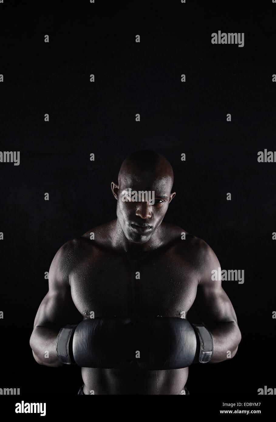 Retrato de profesionales Boxer Masculino contra el fondo negro. Fuerte y musculoso joven en boxeo de marcha. Imagen De Stock