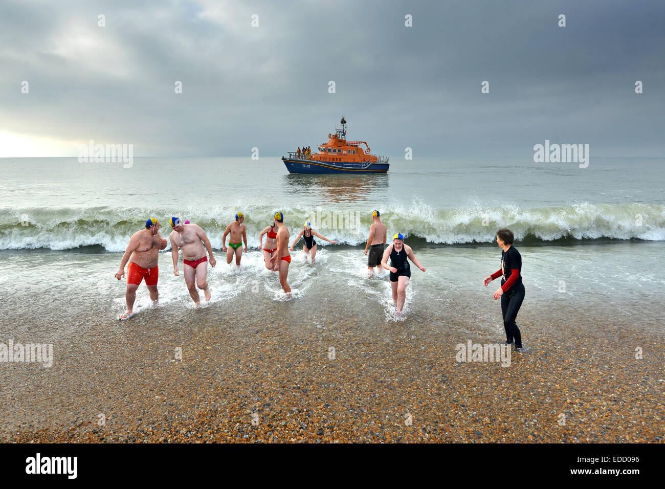 Año Nuevo chapuzón en el mar por socorristas, Seaford Seaford Bay, Sussex, Reino Unido Foto de stock
