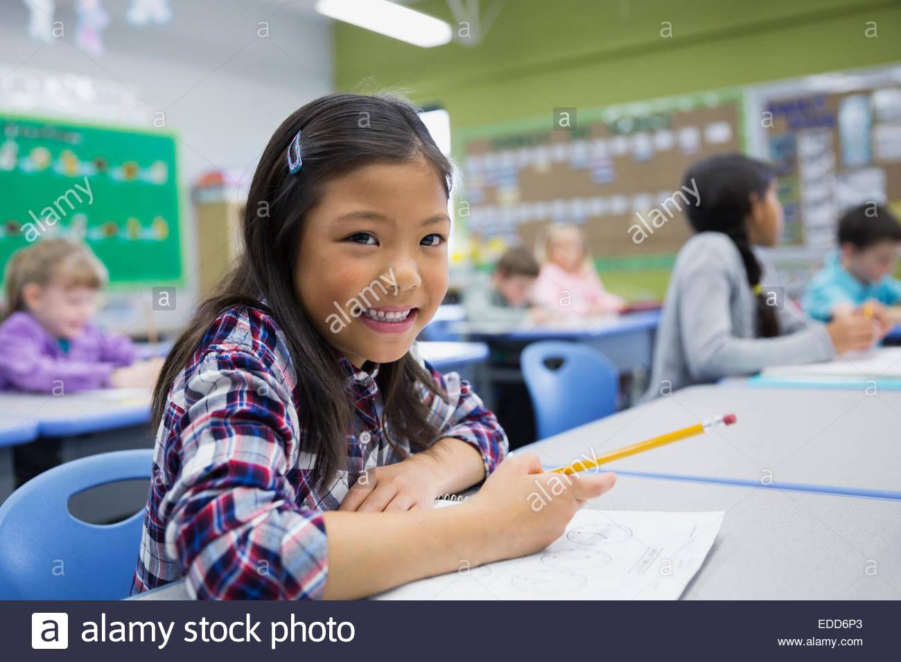 Retrato de sonriente estudiante de primaria en el escritorio Imagen De Stock