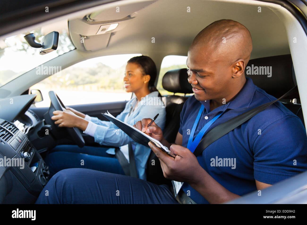 Muchacha africana teniendo prueba de conducción con instructor profesional Imagen De Stock