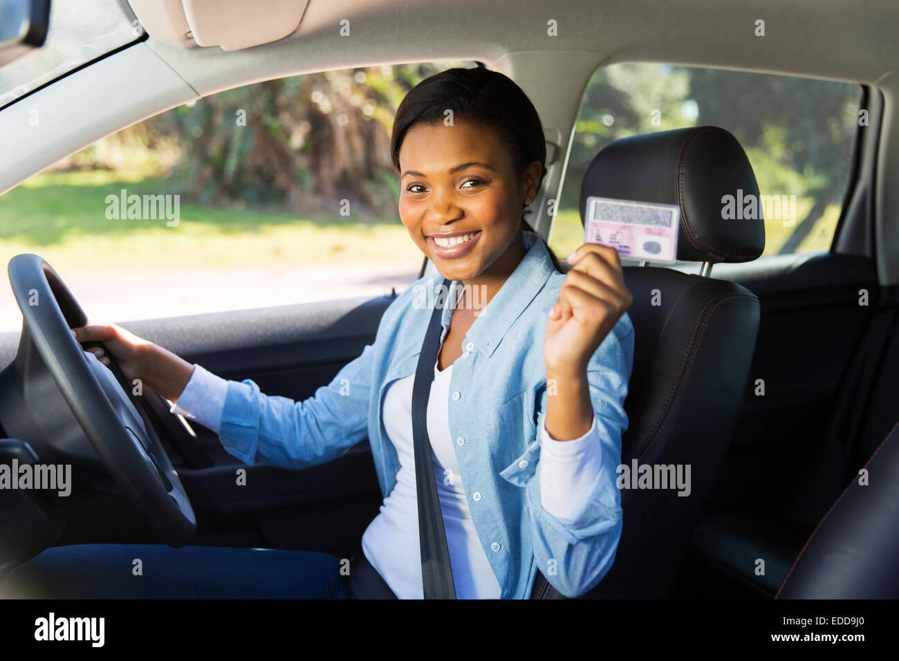 Bonita mujer africana en un coche mostrando su licencia de conductor. Imagen De Stock