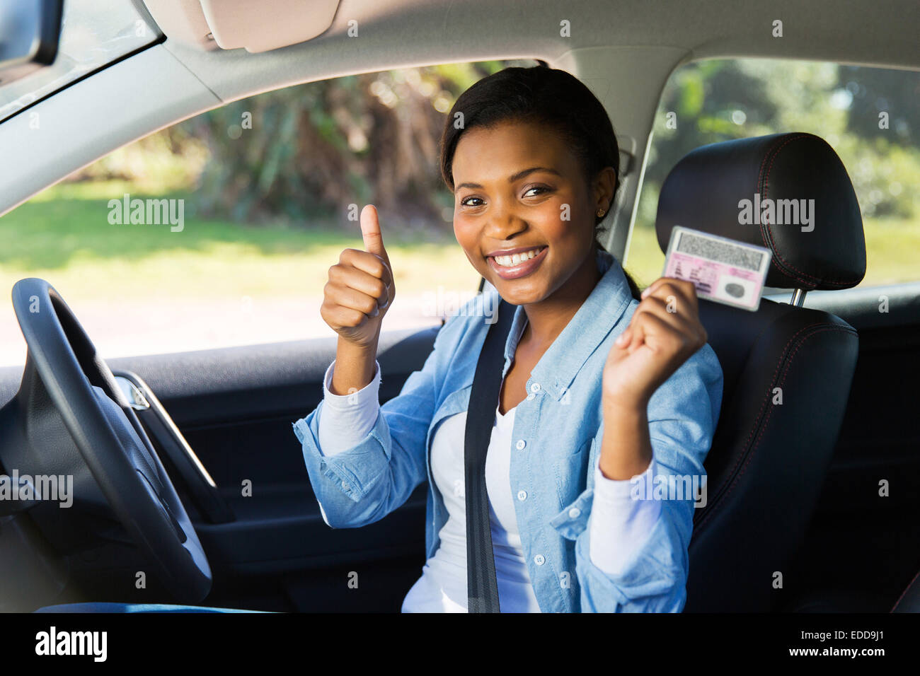 Alegre muchacha africana sosteniendo su licencia de conductor ella acabo Imagen De Stock