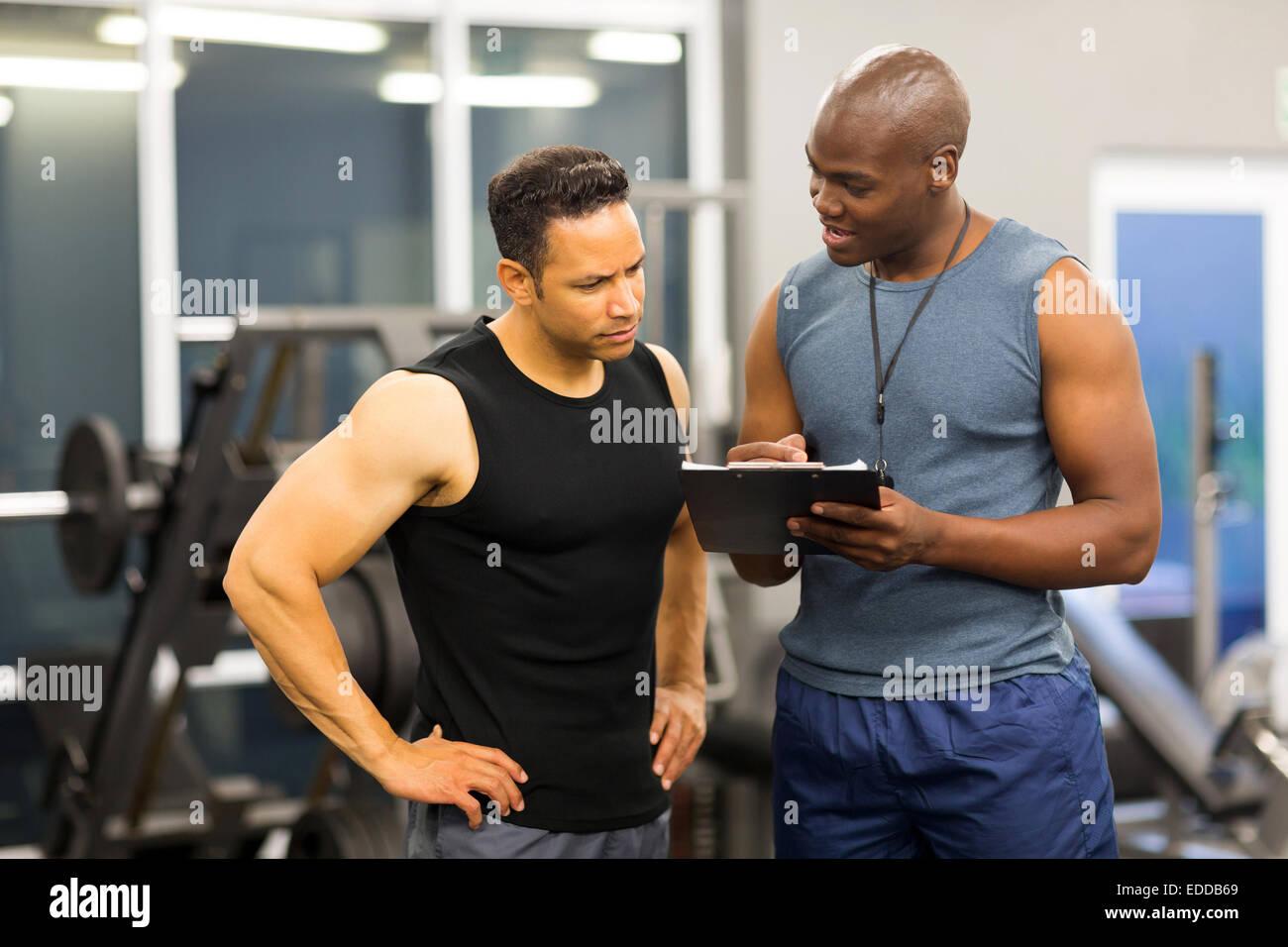 Entrenador personal africano ayudando al hombre para llenar el formulario de afiliación de club de salud Imagen De Stock