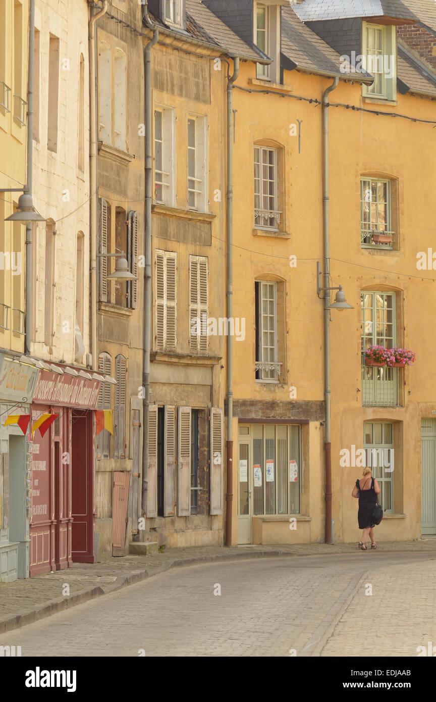 Sedán, Francia - Julio 2013 - Una mujer camina en una calle con casas antiguas en el centro de la ciudad de Imagen De Stock