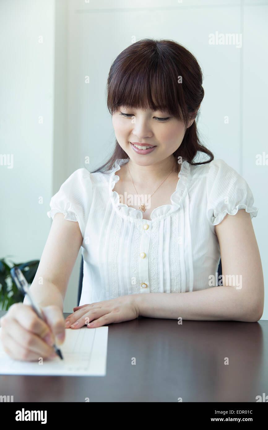 Mujer Rellenar solicitud de trabajo Imagen De Stock