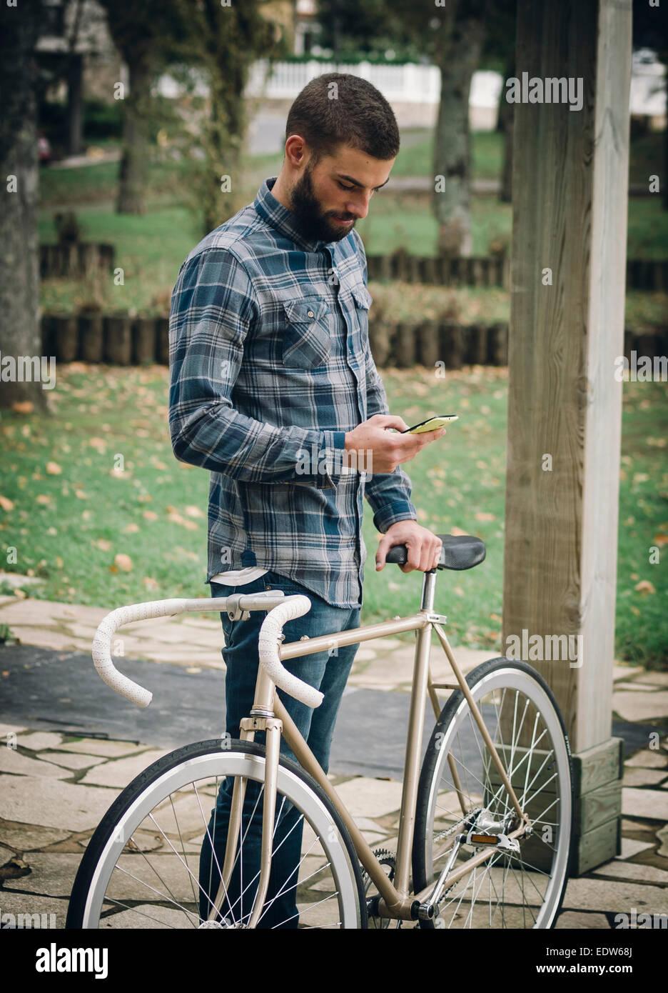 Hipster hombre con una bicicleta fixie y smartphone en un parque al aire libre Imagen De Stock