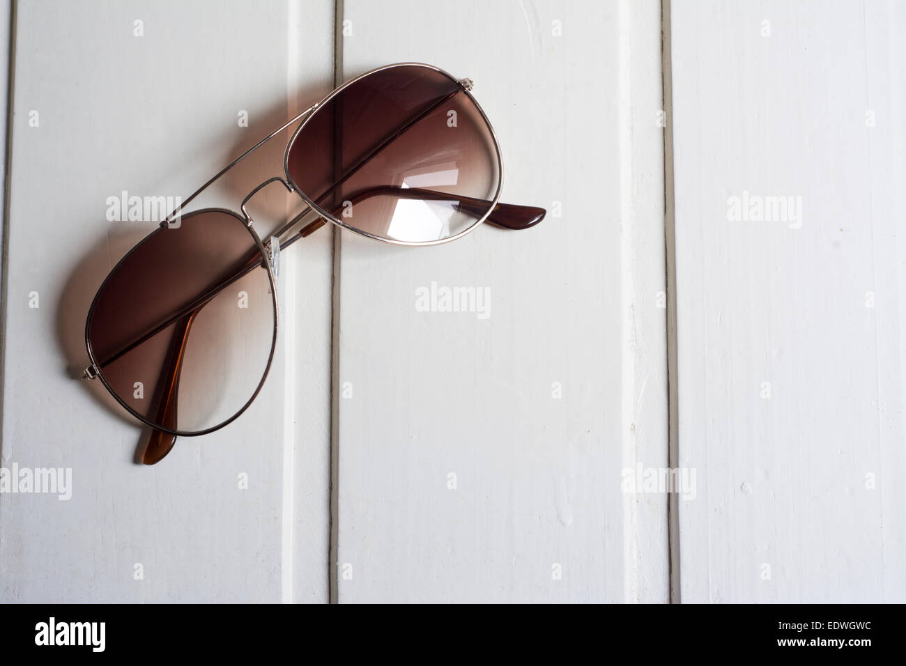 9749b7abec Gafas de sol con cristal marrón sobre fondo blanco de madera Foto ...