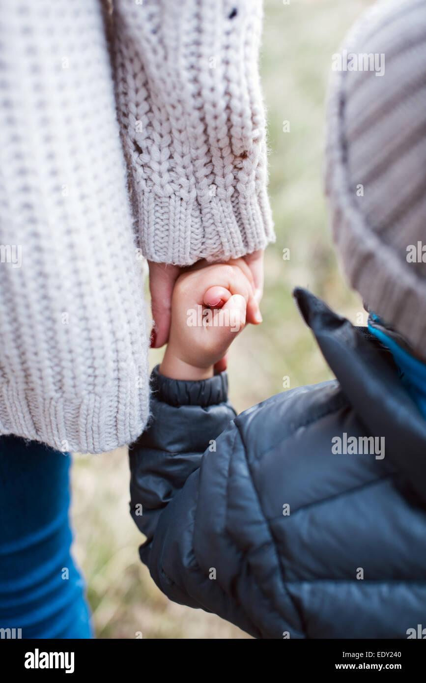 Madre sosteniendo a su hijo por una mano Imagen De Stock