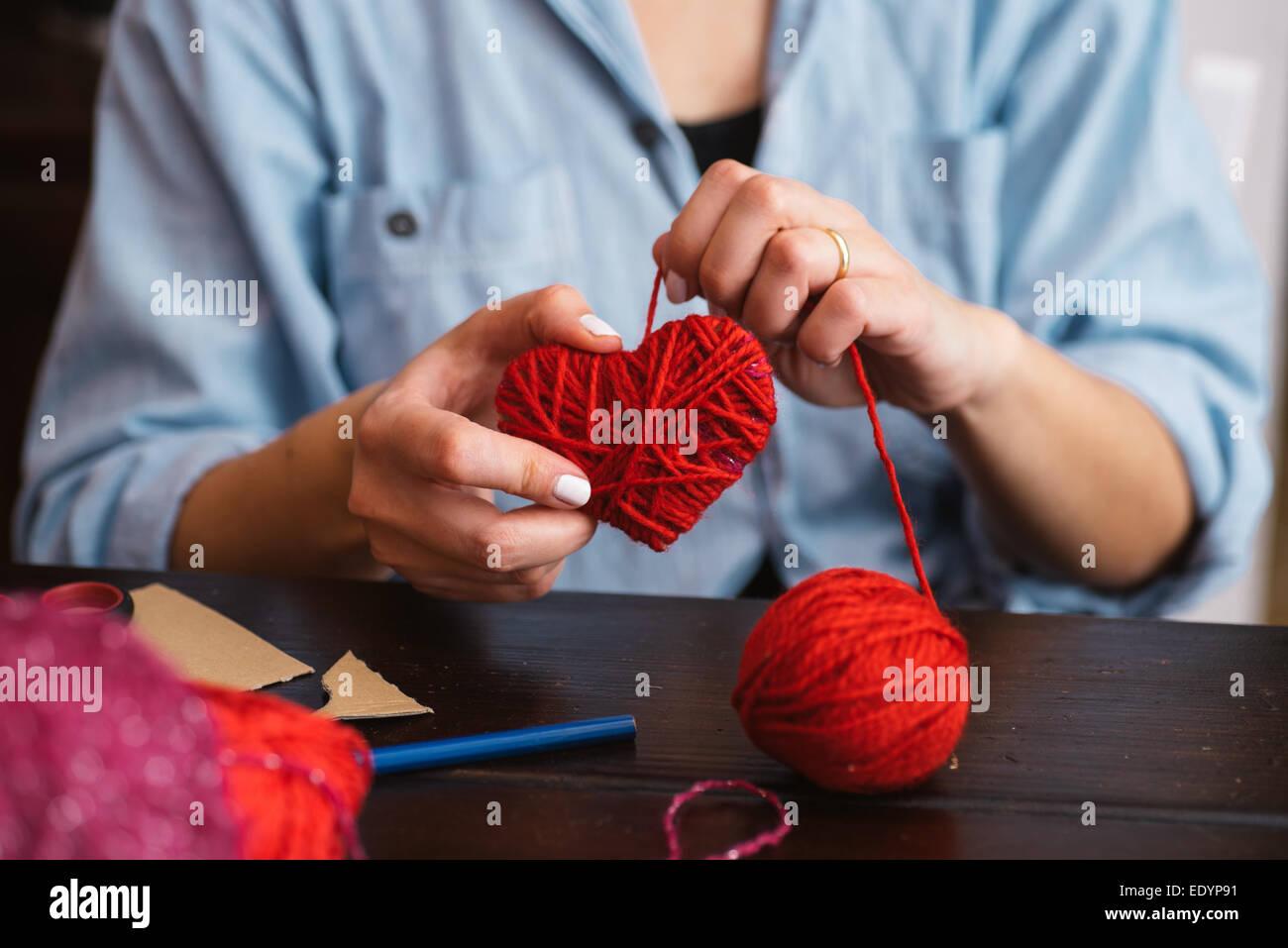 Mujer creación de corazón de lana roja Foto de stock