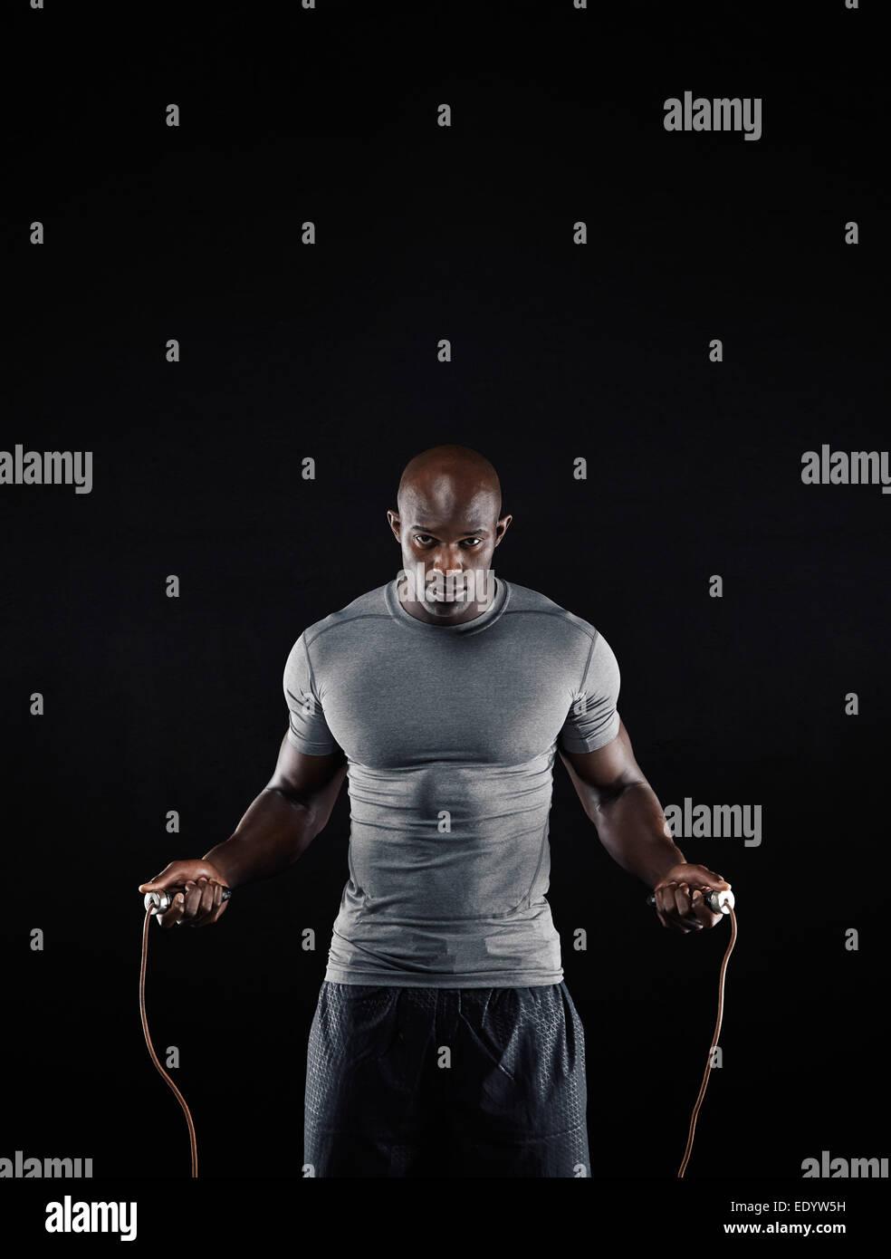 Foto de estudio del hombre africano masculino comba con espacio de copia. Retrato del joven muscular ejercicio de Imagen De Stock