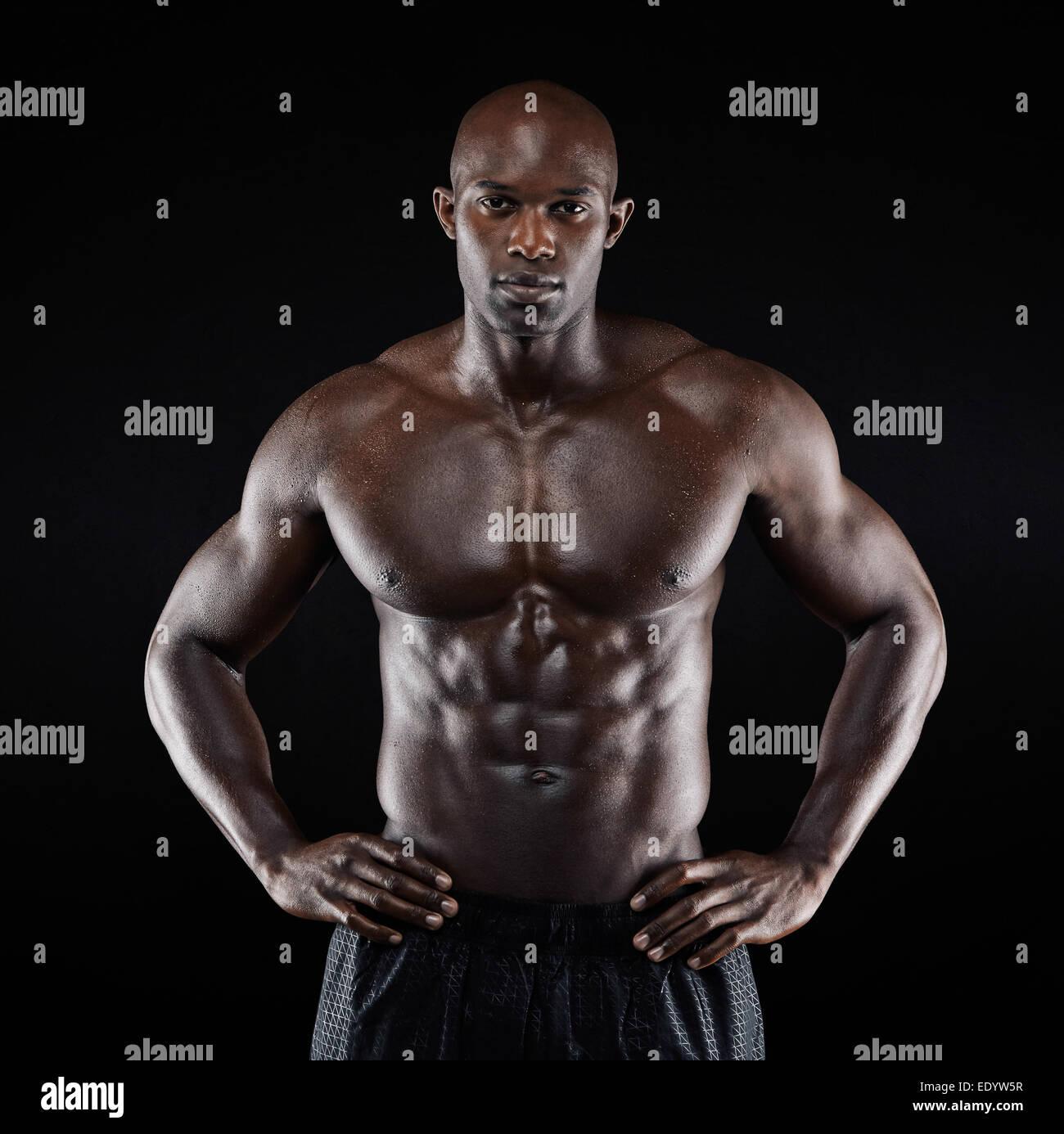 Retrato de un hombre afro-americanos fuertes exhibiendo su cuerpo contra el fondo negro. Descamisados modelo masculino Imagen De Stock