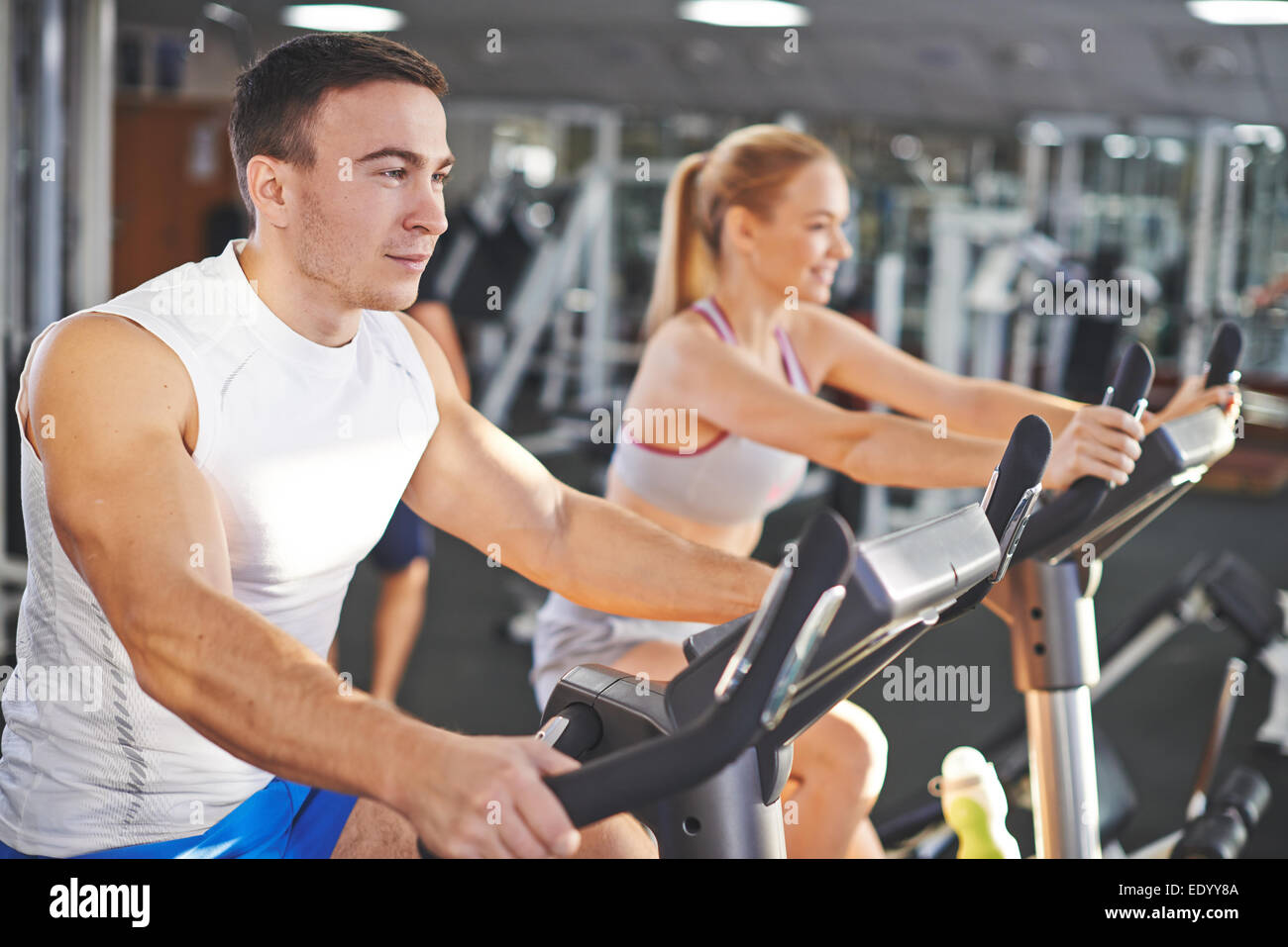 Retrato de hombre joven y mujer durante el entrenamiento en el gimnasio Imagen De Stock