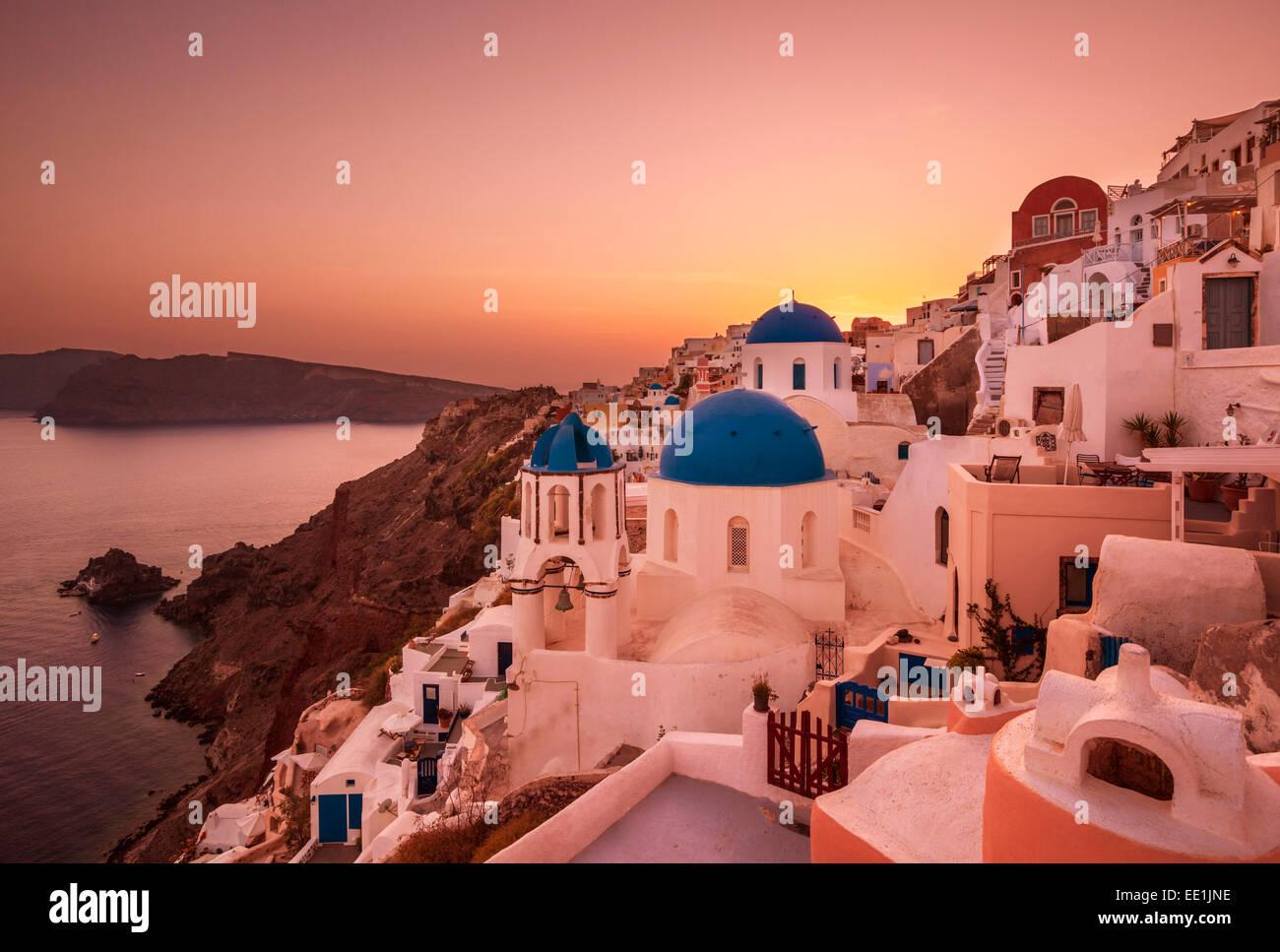 Iglesia griega con tres cúpulas azules en la puesta de sol de Oia, Santorini (Thira), Islas Cícladas, Imagen De Stock