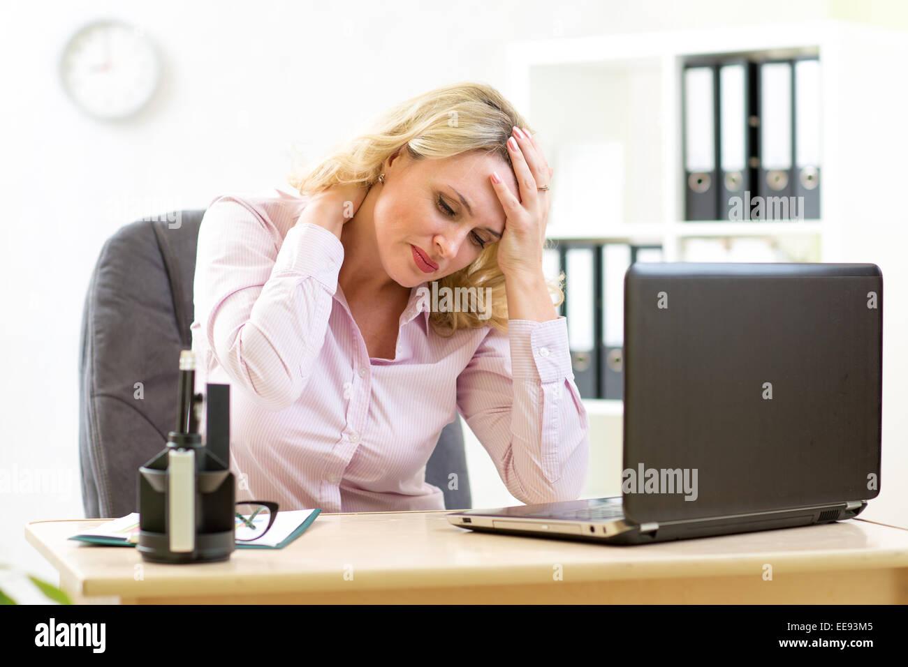 Mujer de negocios con cefalea Tener estrés en la oficina Imagen De Stock