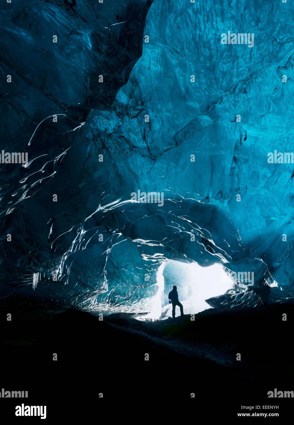 Hombre explorando una impresionante cueva glacial en Islandia Imagen De Stock