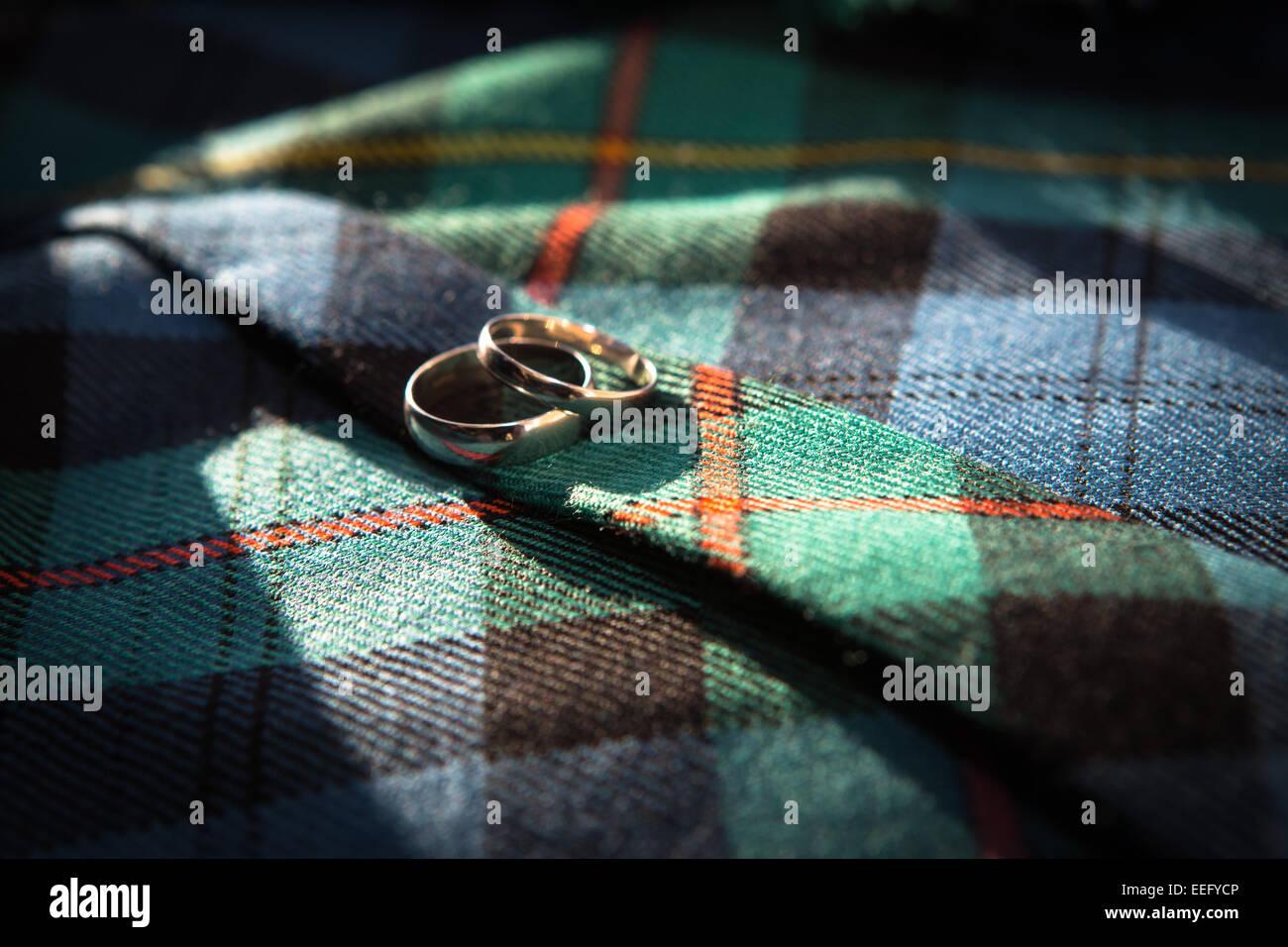 Los anillos de boda Sobre tartan material Imagen De Stock