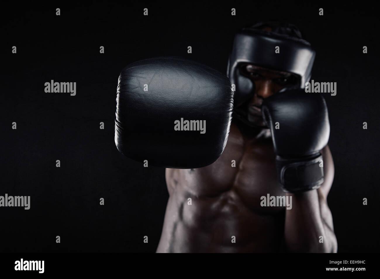 Joven Hombre muscular practicar boxeo. Varón africano arrojando punch hacia la cámara contra el fondo Imagen De Stock