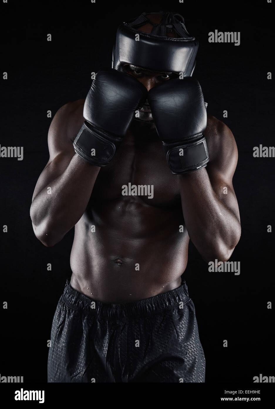 Retrato de un joven boxeador en una postura combativa sobre fondo negro. Varón africano boxer bloqueando su Imagen De Stock