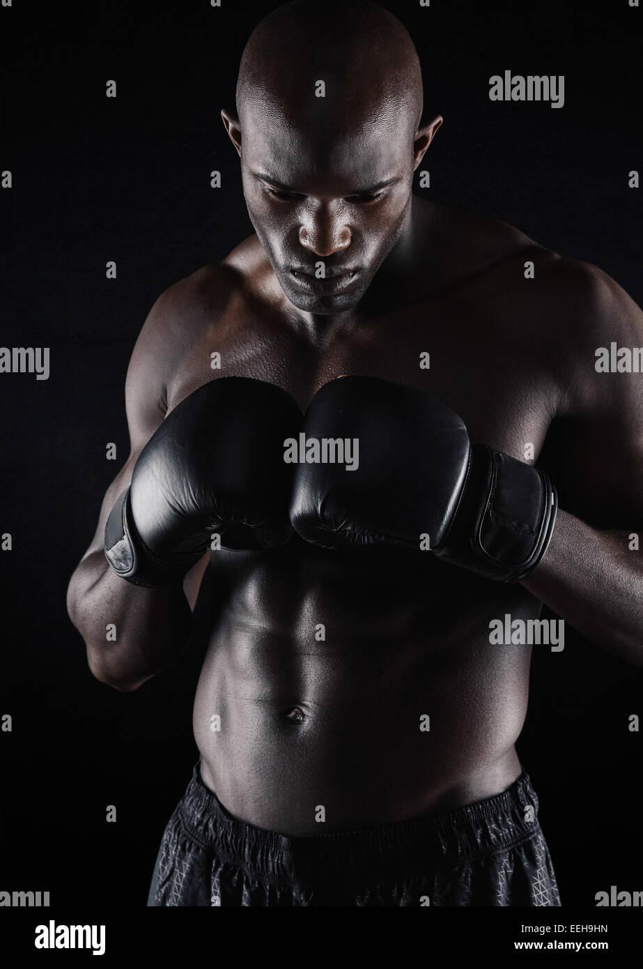 Colocar joven llevando guantes boxeo sobre fondo negro. El boxeador profesional prepara para luchar. Imagen De Stock