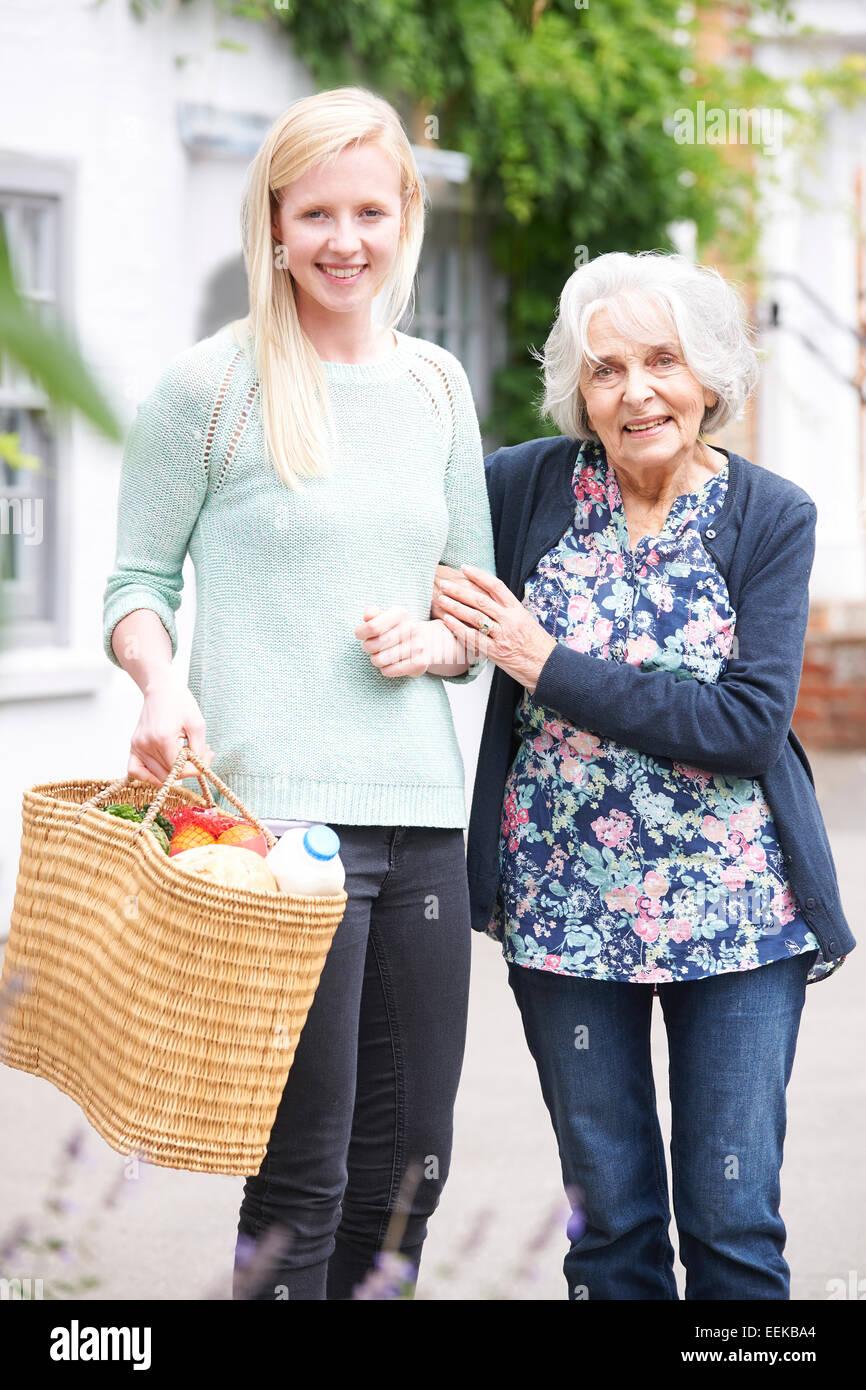 Adolescente ayudar a mujer mayor para efectuar compras Imagen De Stock
