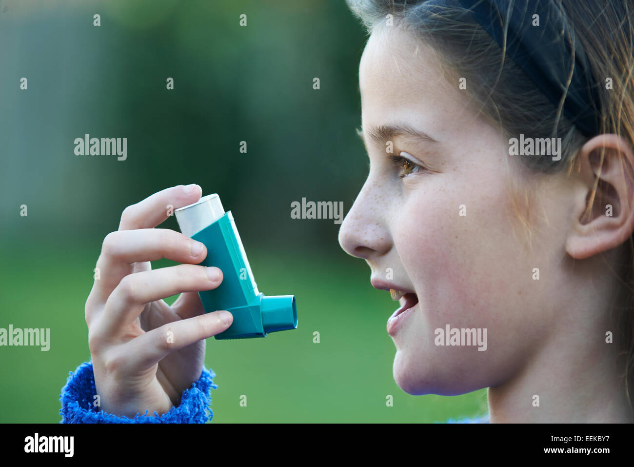 Chica utilizando inhalador para tratar ataques de asma Foto de stock
