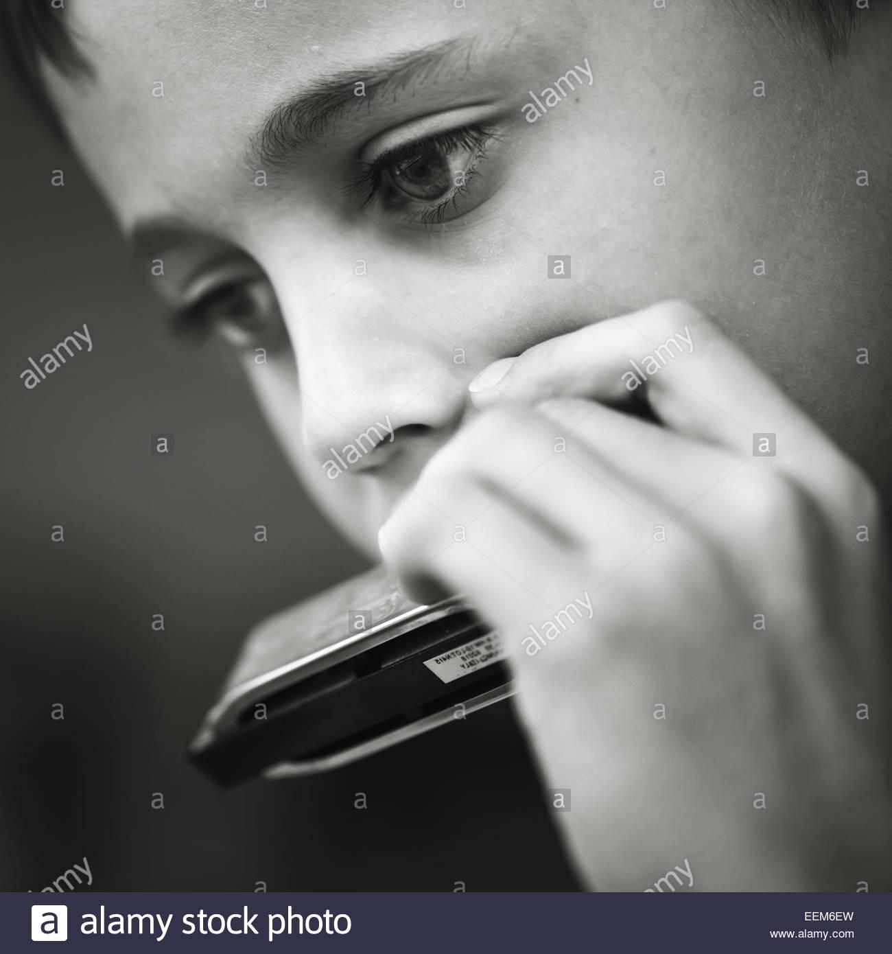 Close-up de boy (8-9) al tocar la armónica Imagen De Stock