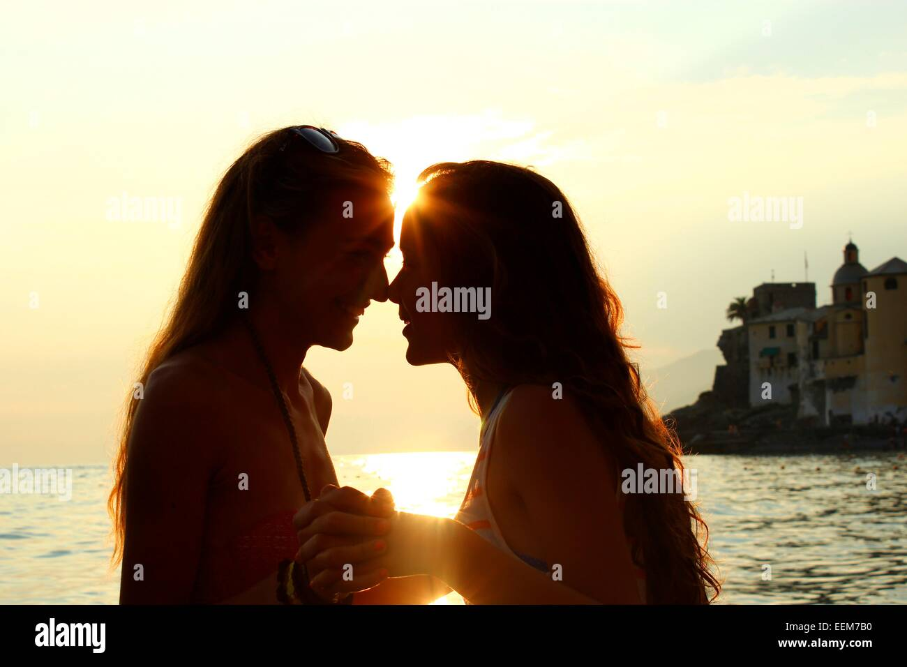 Las mujeres jóvenes cogidos de la mano contra el mar al atardecer Imagen De Stock