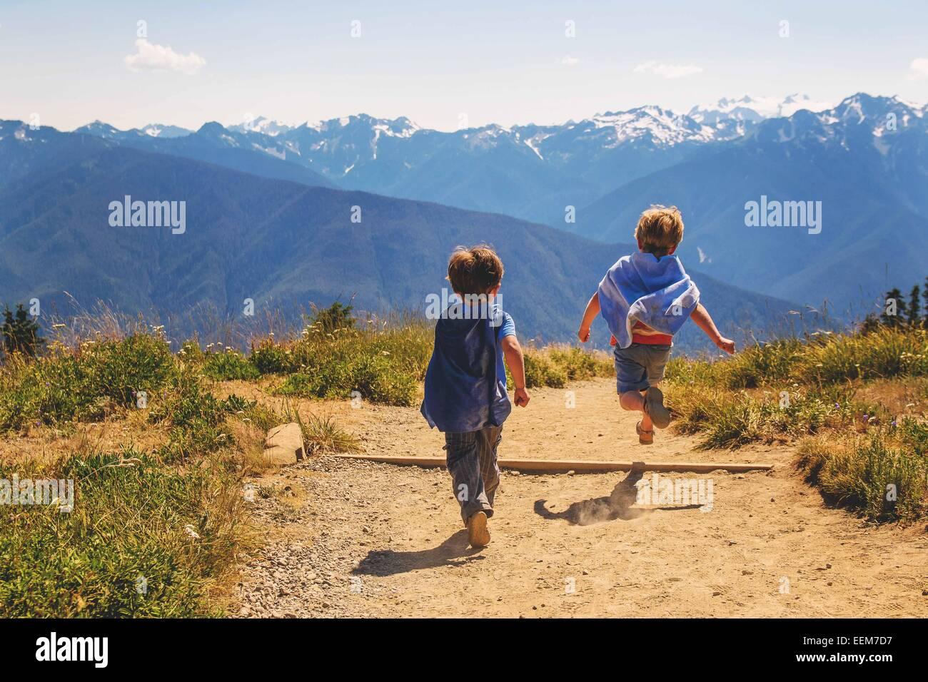 Dos chicos jóvenes (2-3, 4-5) vistiendo super hero capes girando en la montaña Imagen De Stock