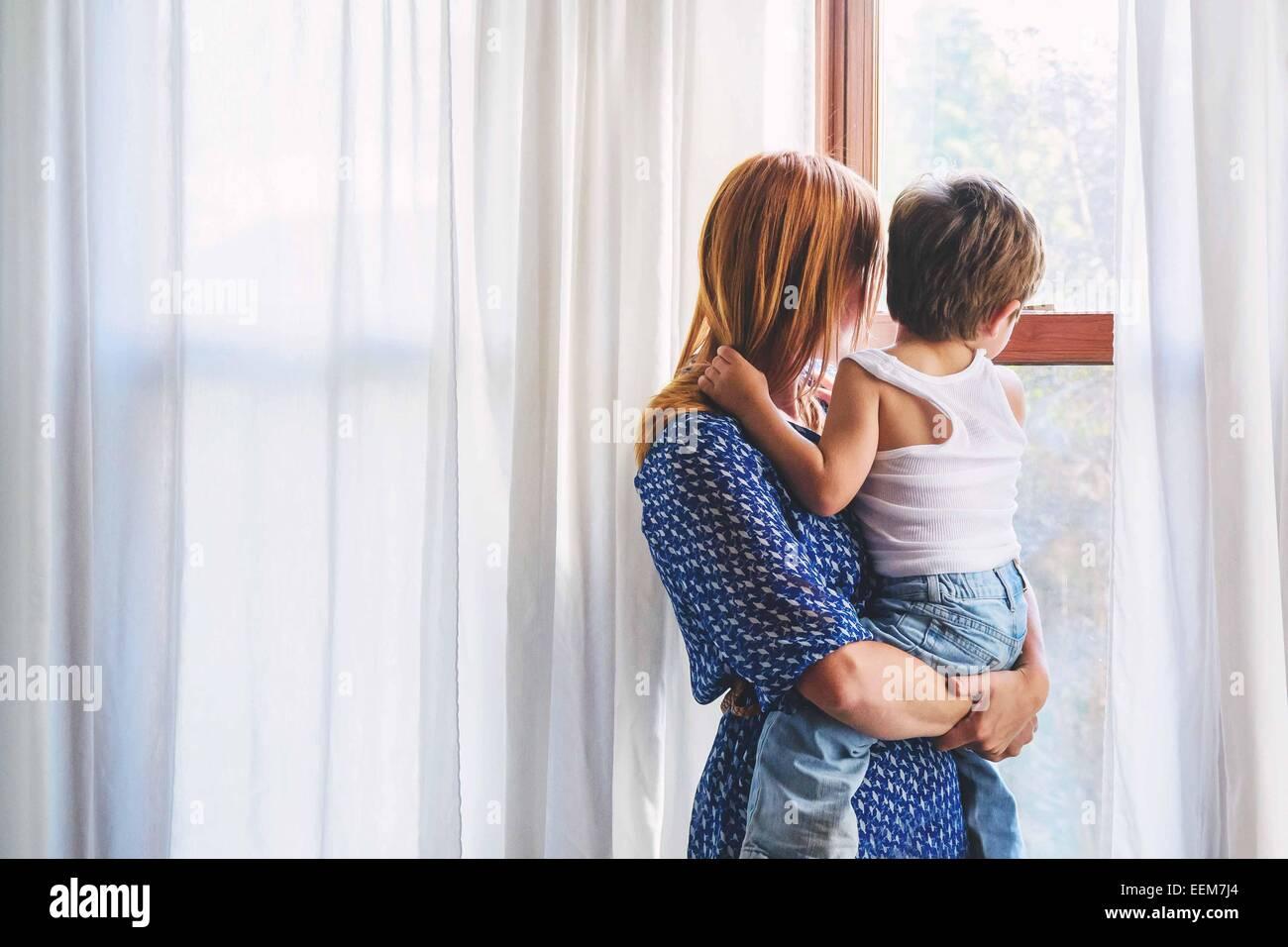 La madre y el niño (2-3) niño mirando hacia afuera de la ventana Imagen De Stock