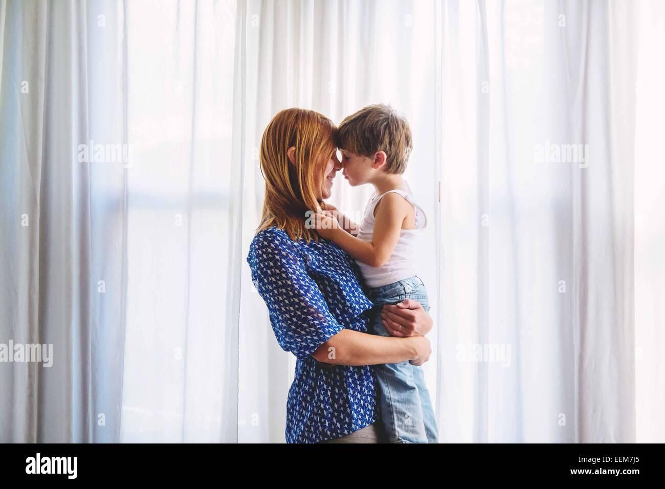 Mamá mantiene joven (2-3) y tocando las narices Imagen De Stock