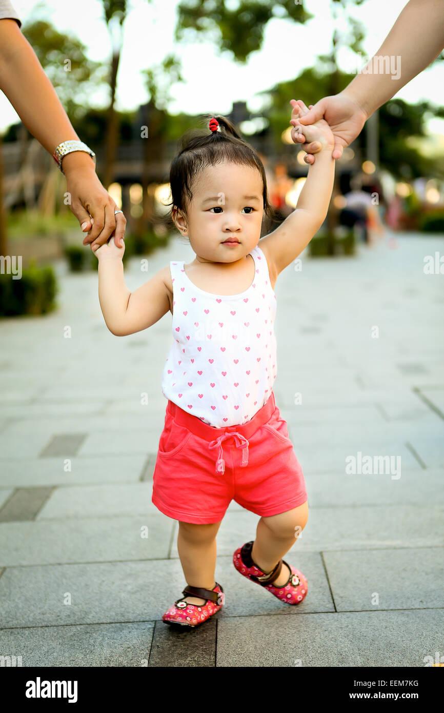 Chica (2-3) caminar mientras los adultos se mantenga sus manos Imagen De Stock