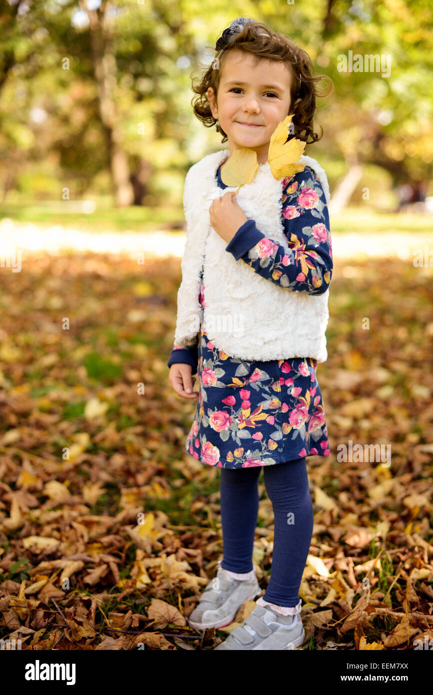 Retrato de niña (4-5) disfrutando y jugando con las hojas de otoño en el parque Foto de stock