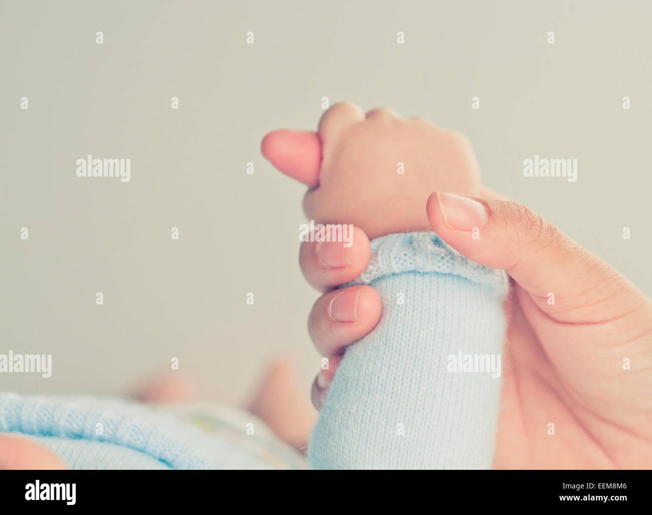 La madre la mano que sostiene la mano de bebé Imagen De Stock