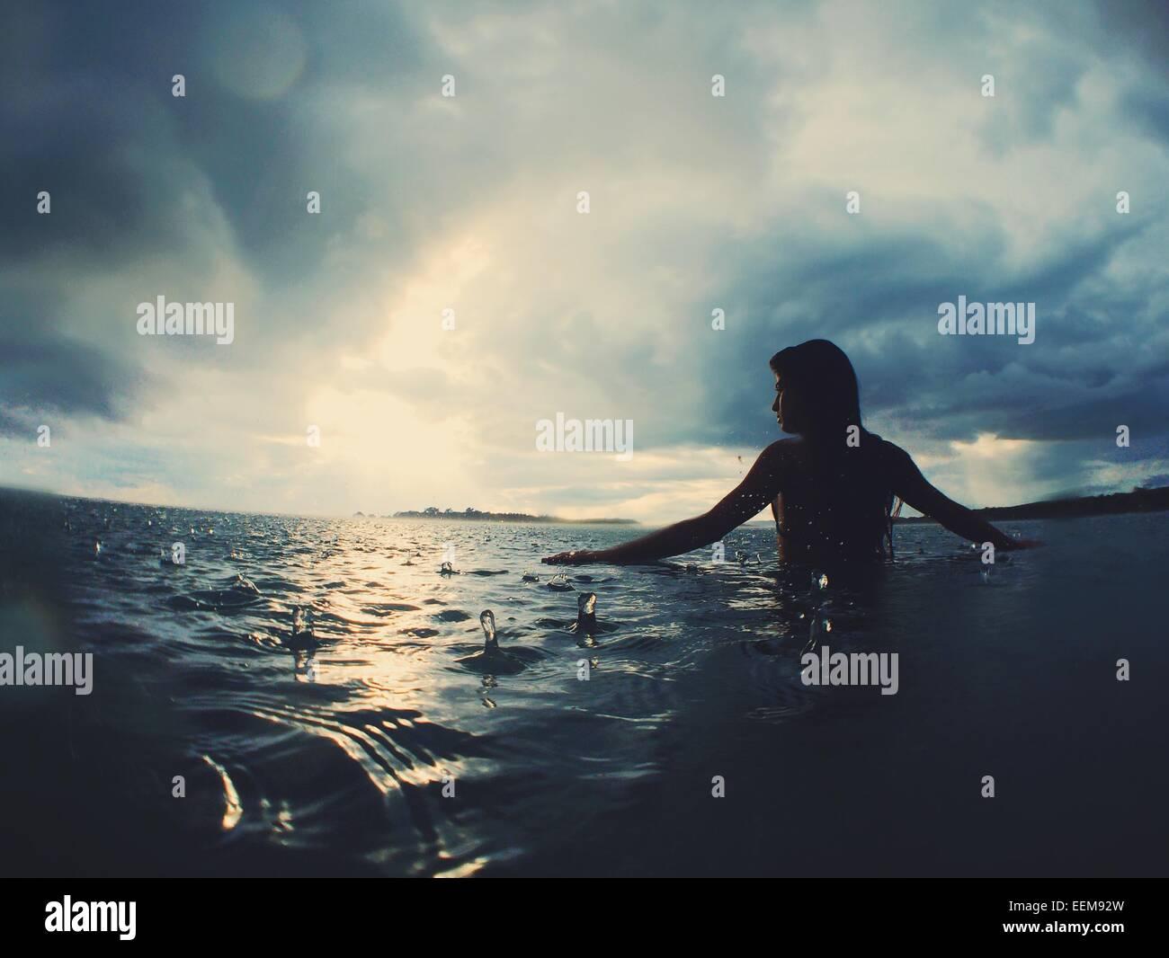 Mujer en el mar bajo la lluvia Imagen De Stock