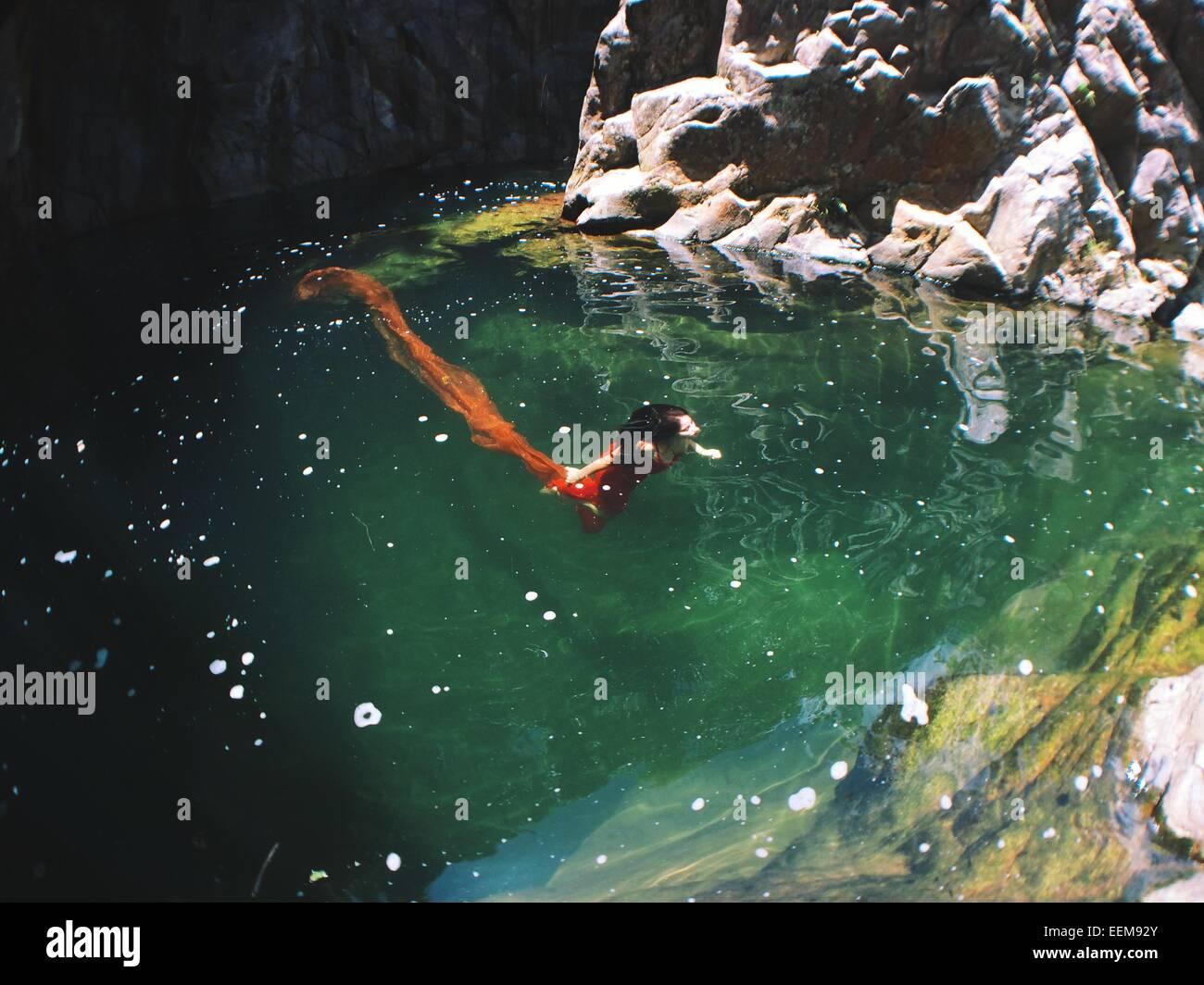 Mujer de vestido rojo bajo el agua Imagen De Stock