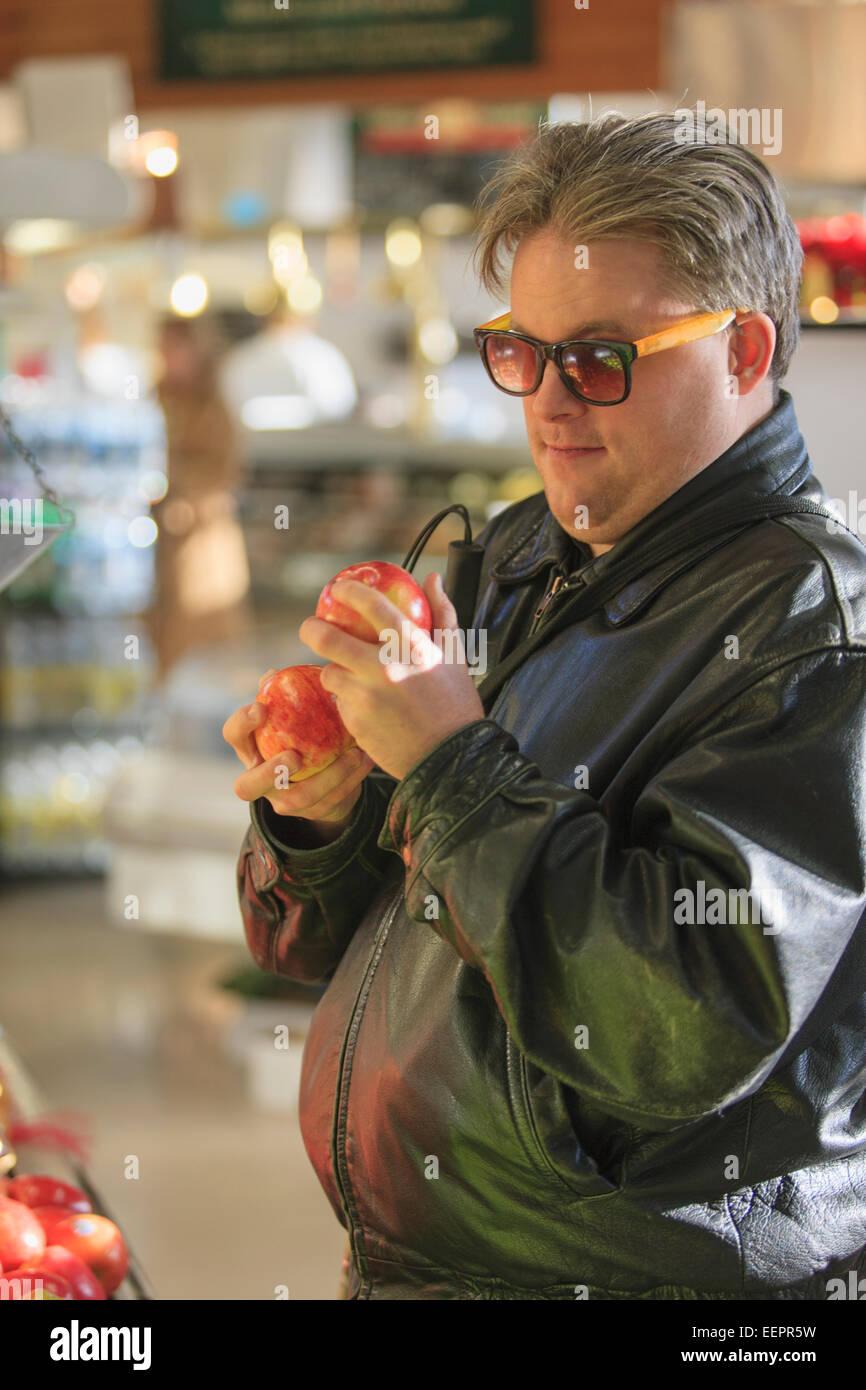 Hombre con ceguera congénita en la tienda sacando fruto Imagen De Stock