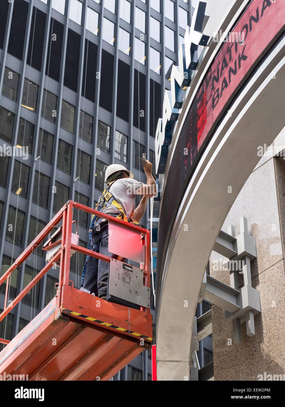 Reparación del banco . Un trabajador ejerce un martillo mientras trabaja en la reparación o instalación Imagen De Stock