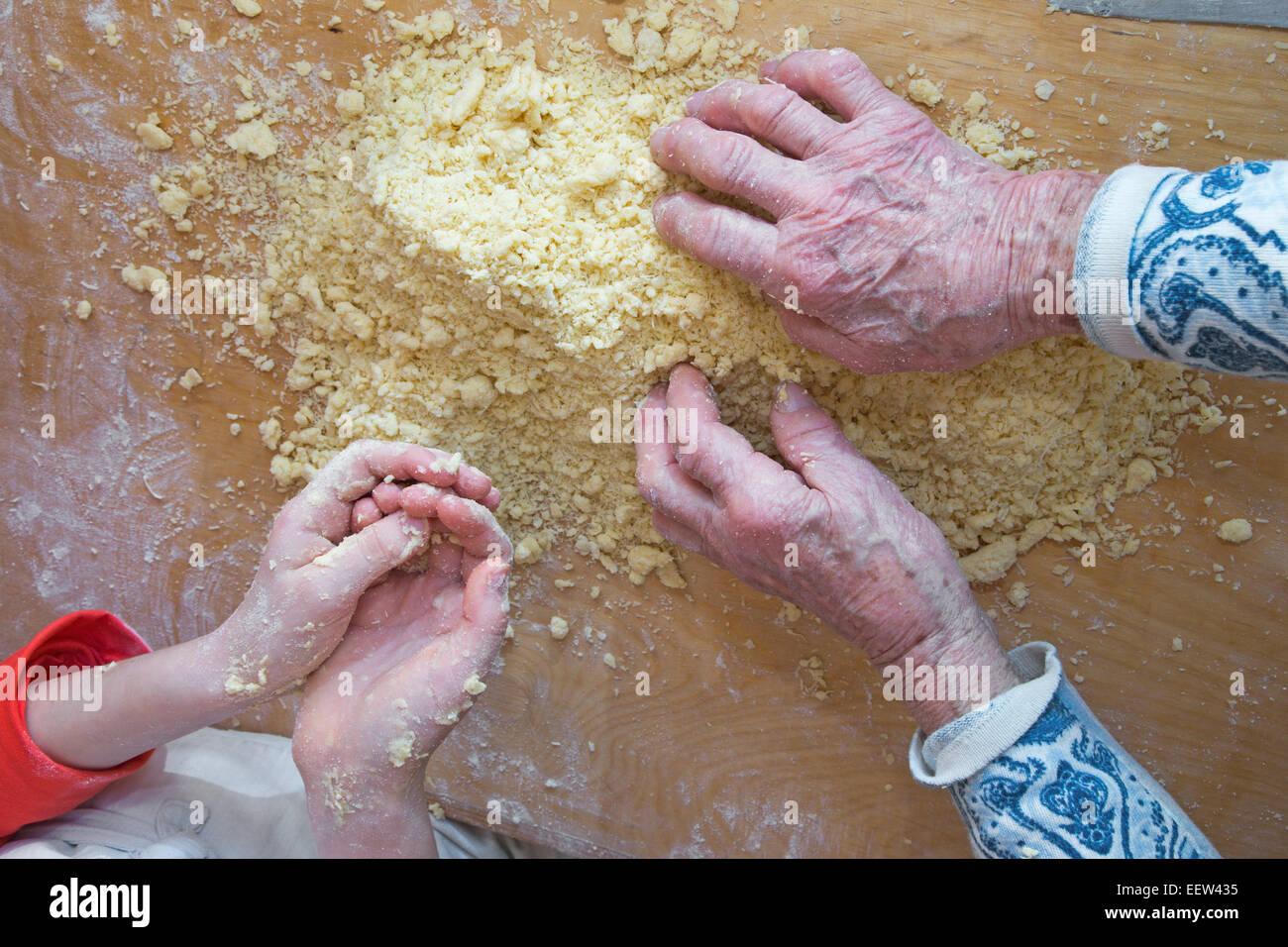 Las manos de la abuela y su nieto en la cocina Foto de stock