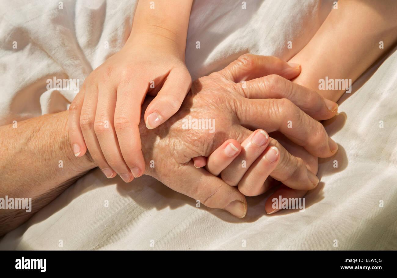 Las manos de la abuela y su nieto en la cama Imagen De Stock
